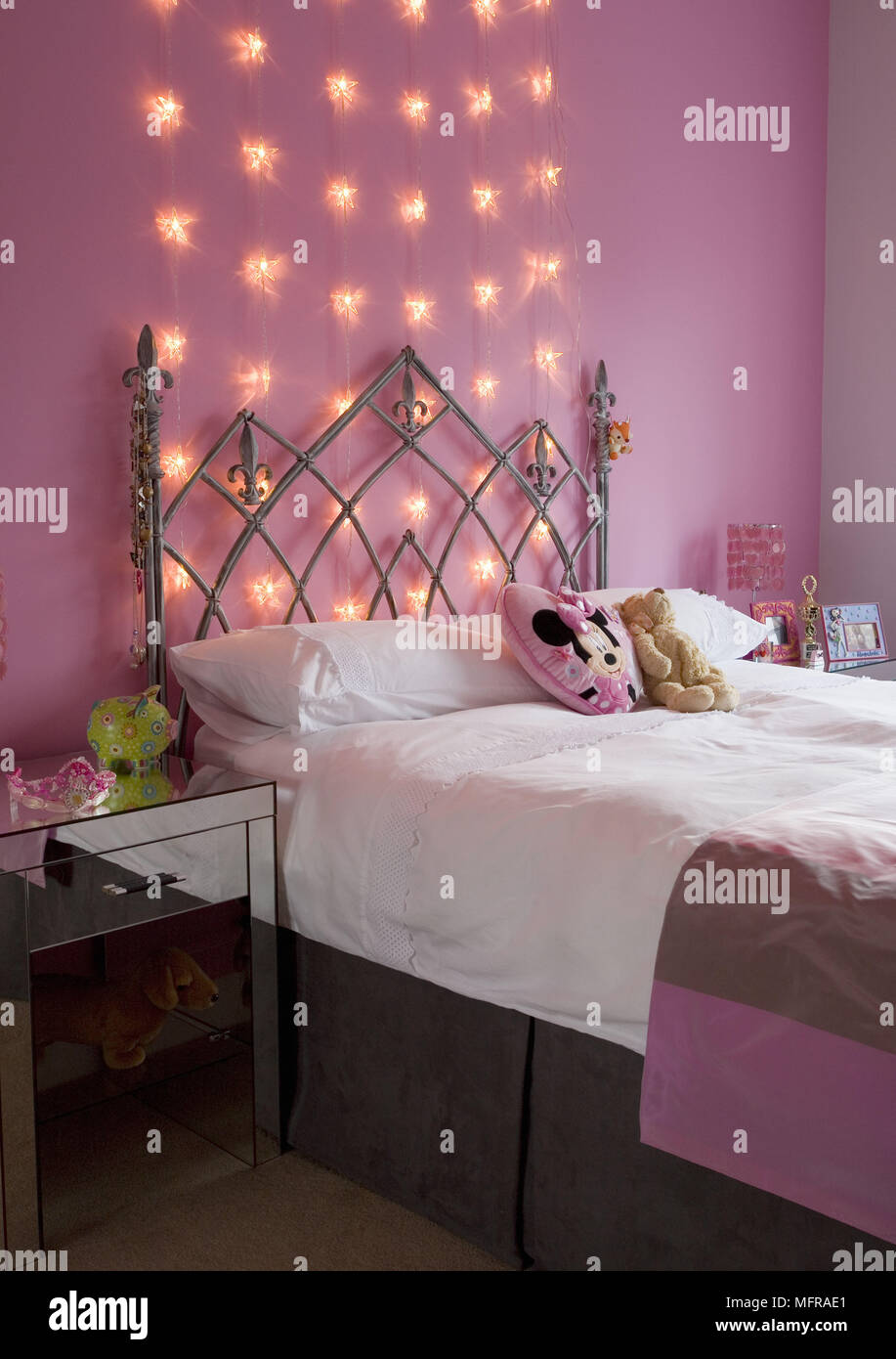 Wrought iron double bed in pink bedroom with fairy lights on ...