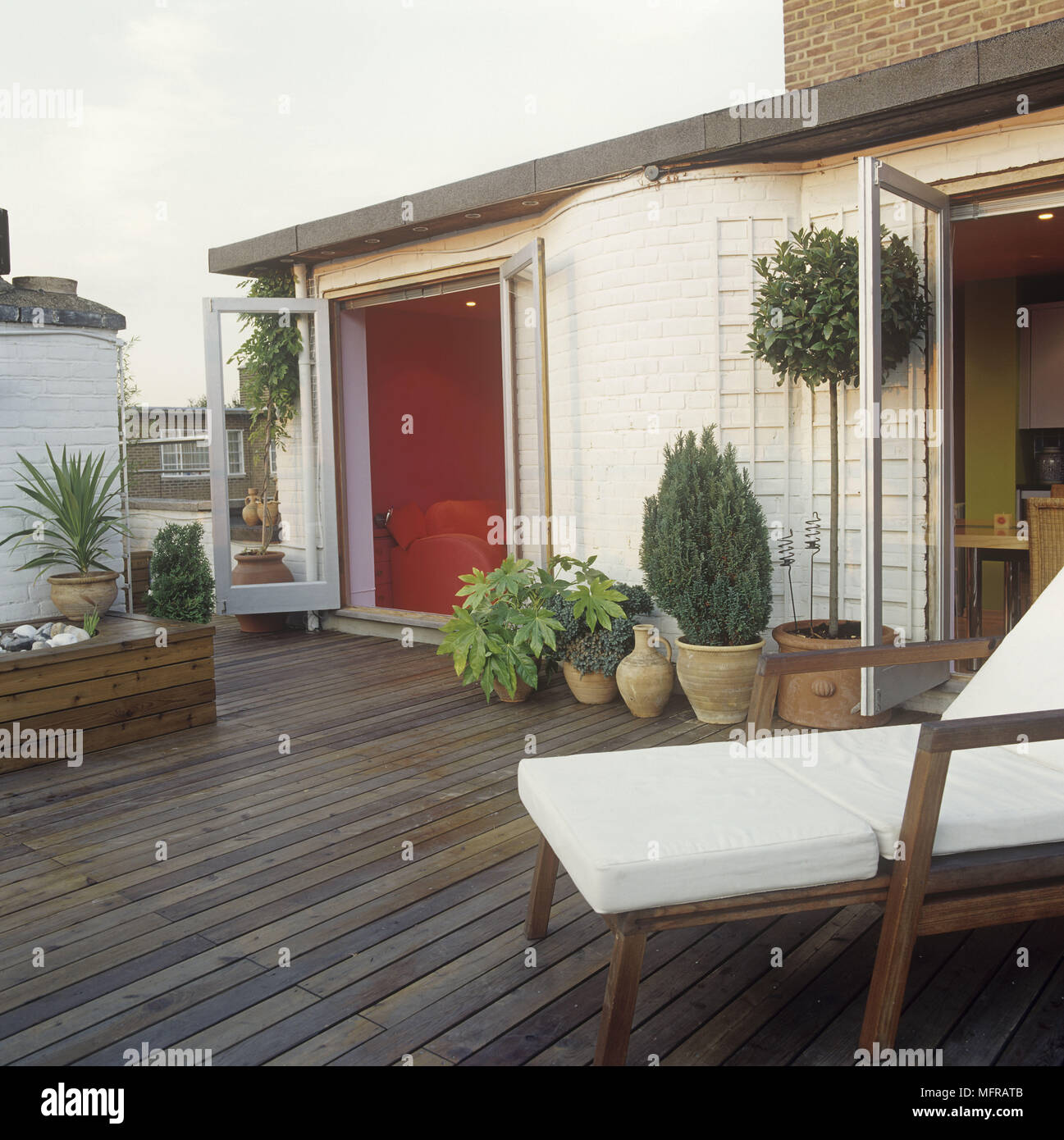 Decked Patio Area With Sun Lounger And Potted Plants