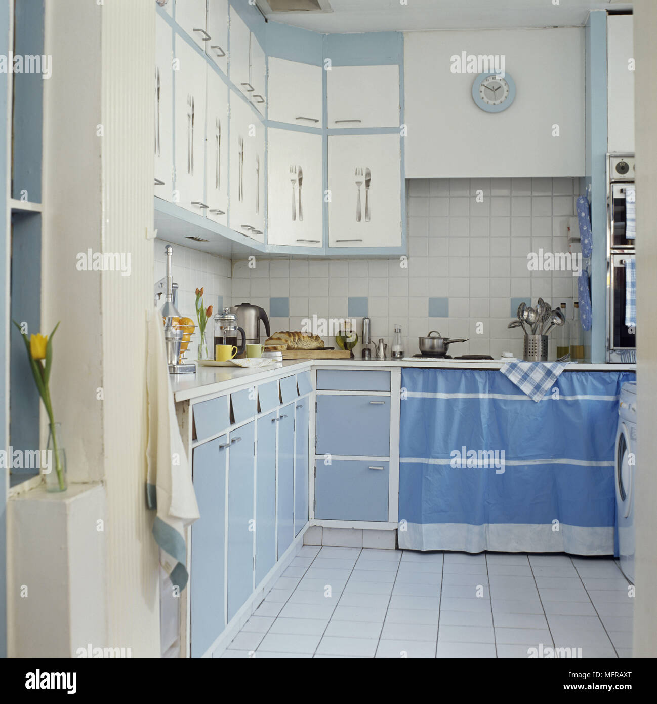 Kitchen with blue and white cupboard units and tiled walls Stock ...