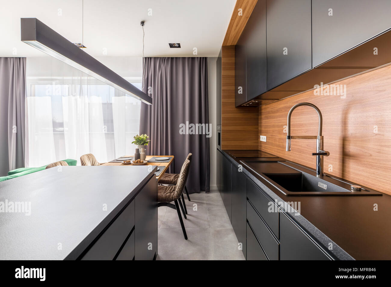 Kitchen interior with black cabinets, steel tap and wooden table in dining area - Stock Image