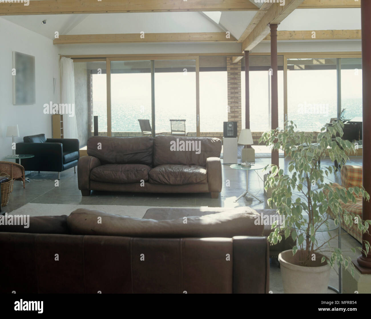 Leather settees in large sitting room with exposed timber railing and large windows - Stock Image