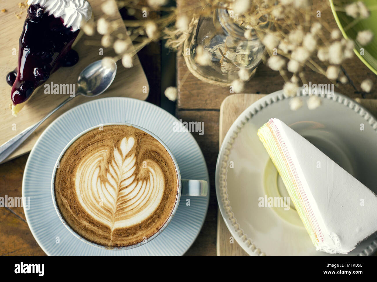 Cappuccino coffee with latte art and cake slice desserts - Stock Image