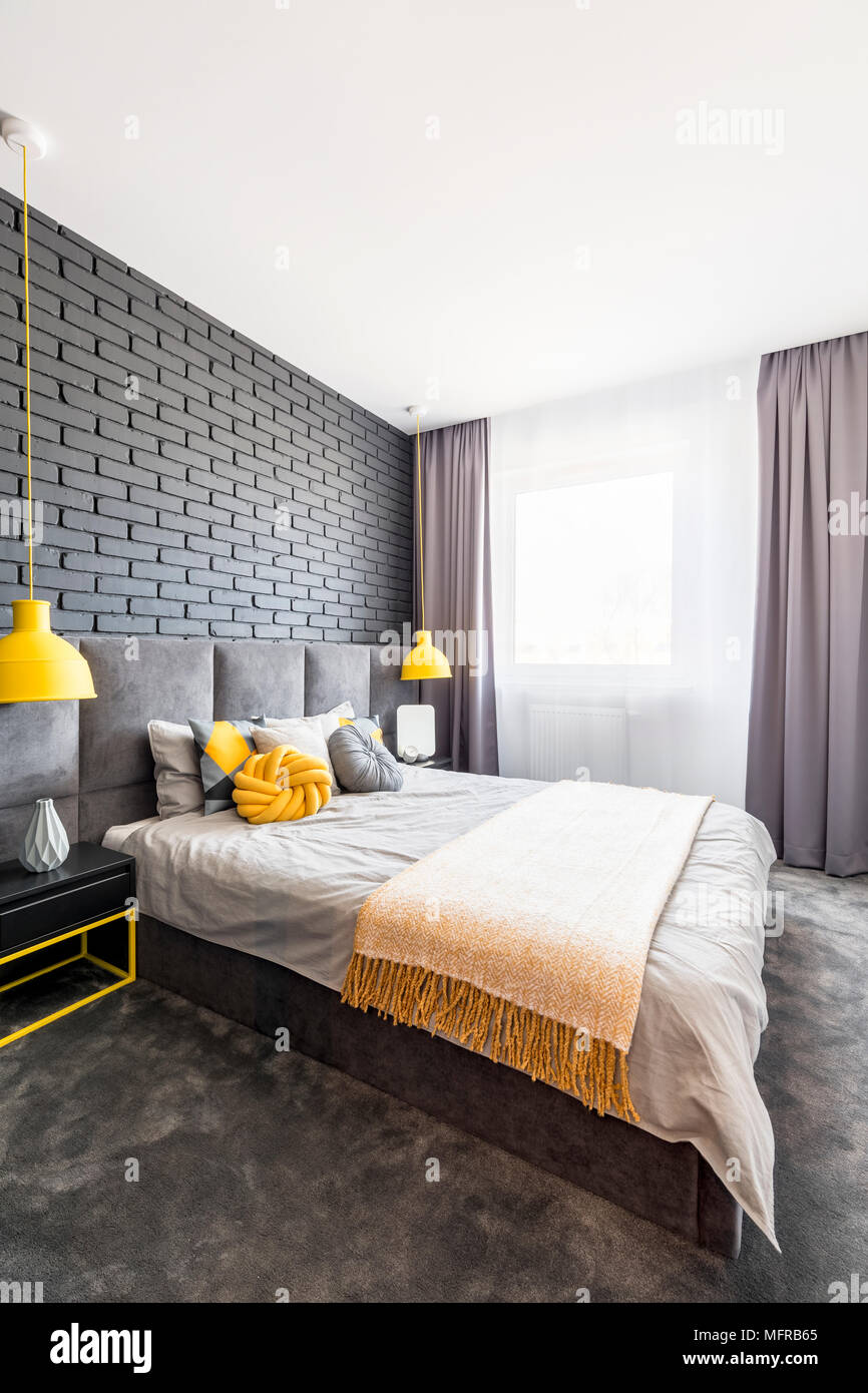 Charming Modern, Gray And Yellow Bedroom Interior With Comfy Bed Standing Against  Black, Brick Wall Between Yellow Lamps