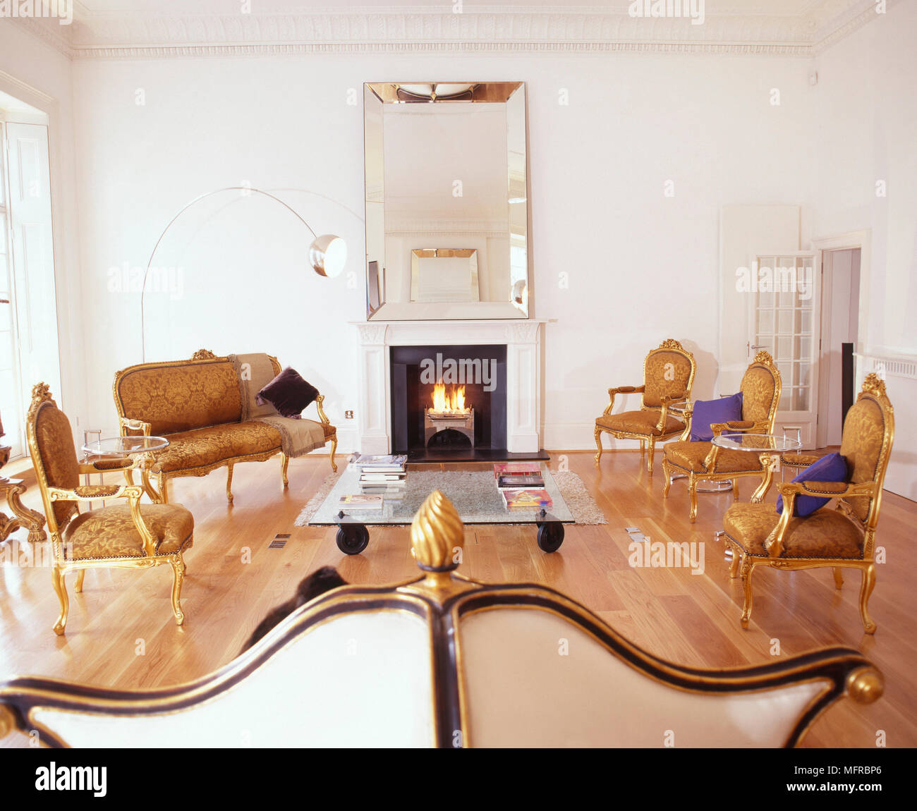 Sitting room with gilded antique chairs, chrome and glass tables, wood  floor, and a large, frameless mirror over a lit fireplace. - Sitting Room With Gilded Antique Chairs, Chrome And Glass Tables