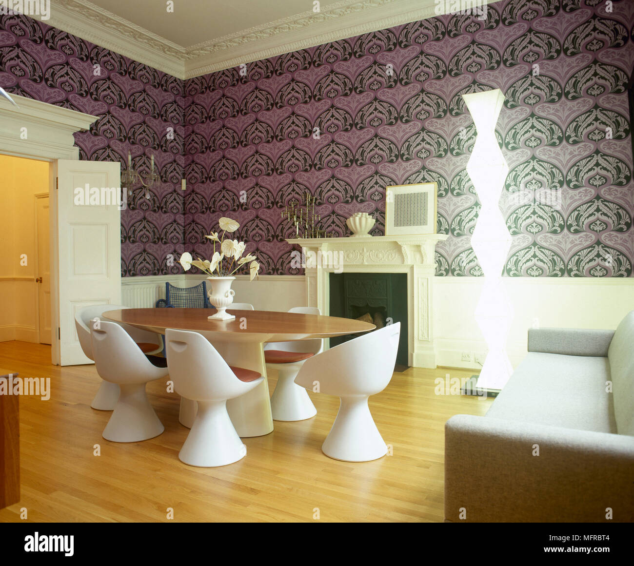 Modern Dining Room With Geometric Wallpaper Table Moulded Plastic Chairs Wood Floor And A Lit Sculptural Lamp
