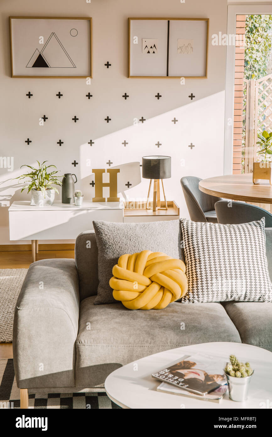 Yellow Handmade Knot Cushion Placed On Grey Couch In White Living Room Interior With Crosses And Simple Posters On The Wall Stock Photo Alamy