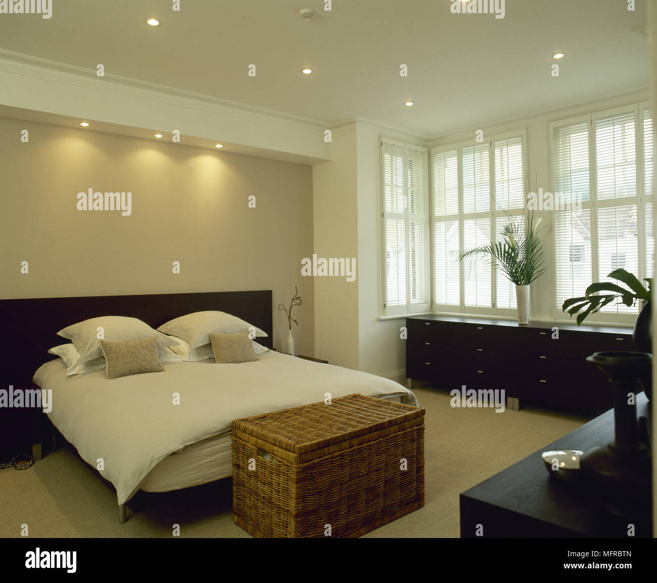 Modern Bedroom With Double Bed, Black Wood Furnishings, Recessed Lighting,  And Bay Window.