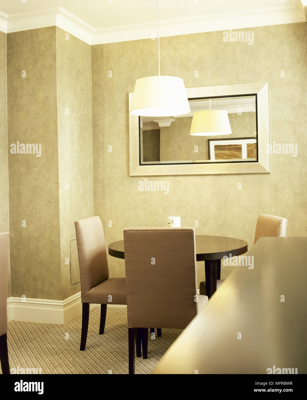 Modern Dining Room With A Round Dining Table And Upholstered Chairs Carpeted Floor And Hanging Lamp Stock Photo Alamy