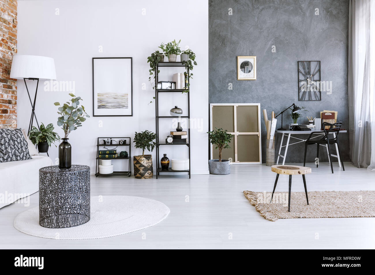 Grey home office with plants, metal coffee table and raw, concrete wall - Stock Image