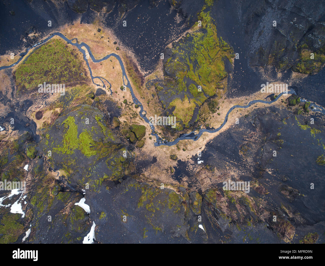 Aerial view of rugged icelandic terrain with little stream in between black rock formations in Iceland - Stock Image
