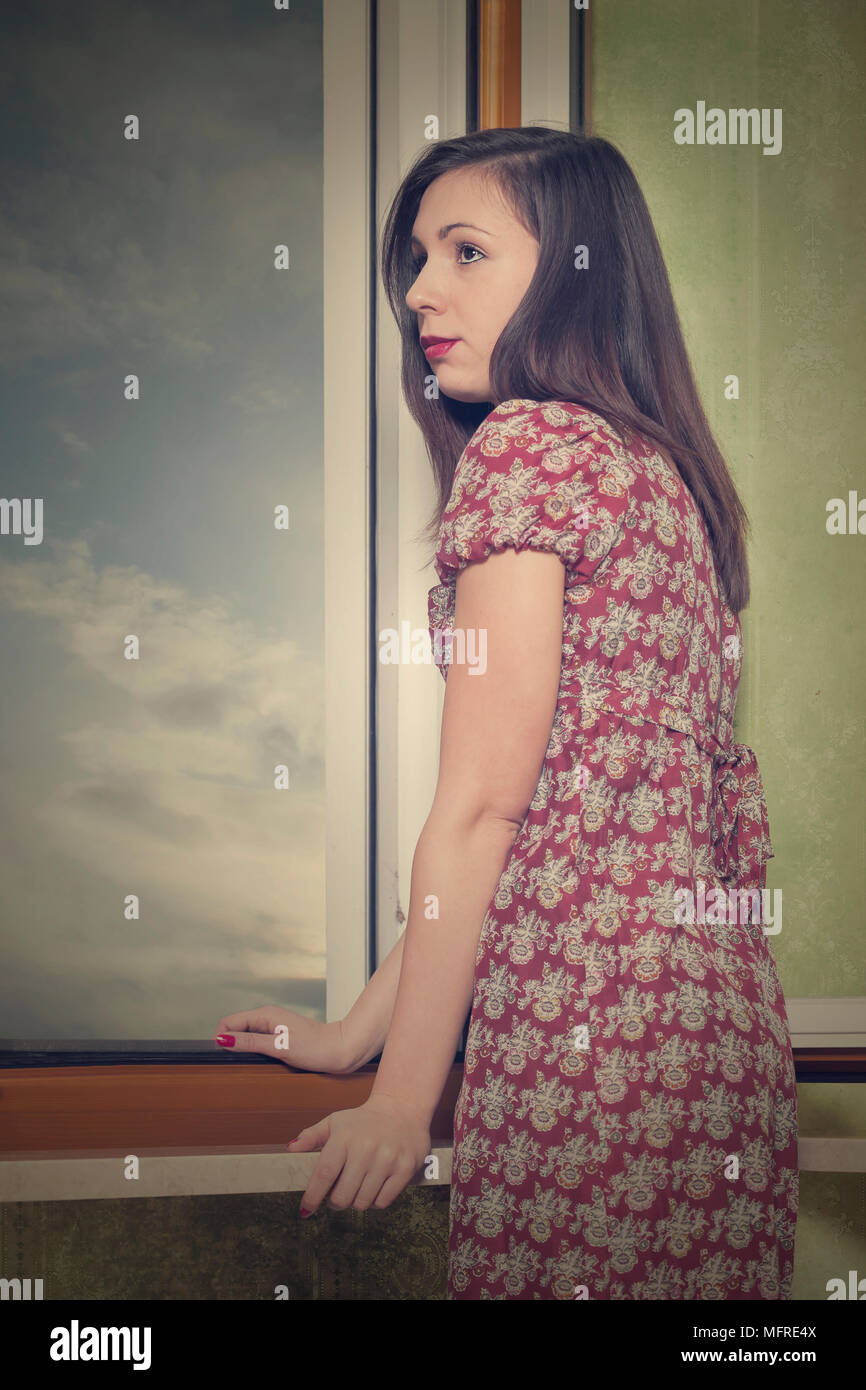 a woman in a floral dress is standing next to an open window - Stock Image