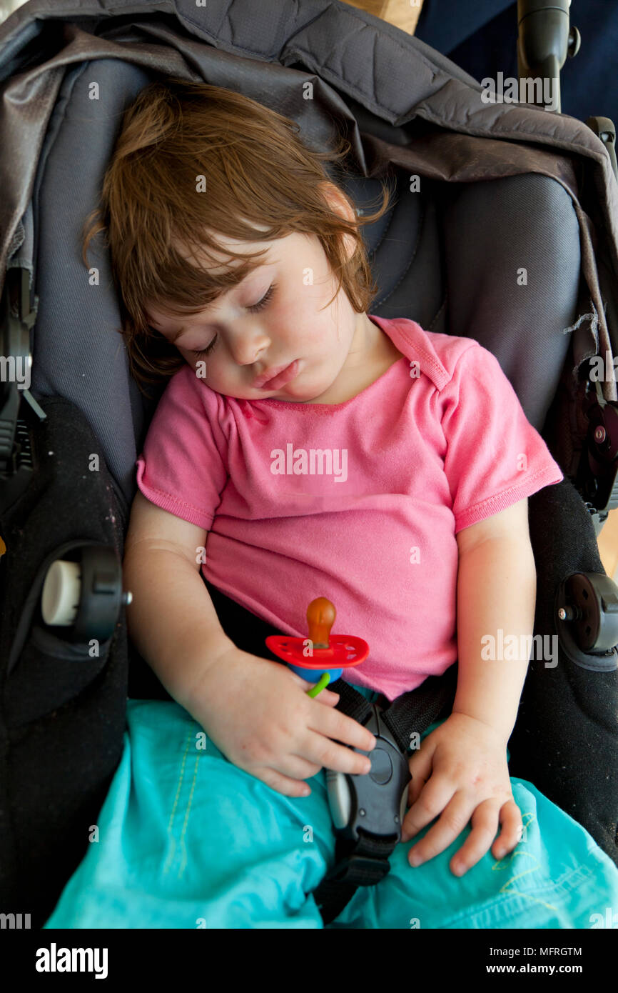 baby toddler sleeping in pram with pacifier in hand stock photo