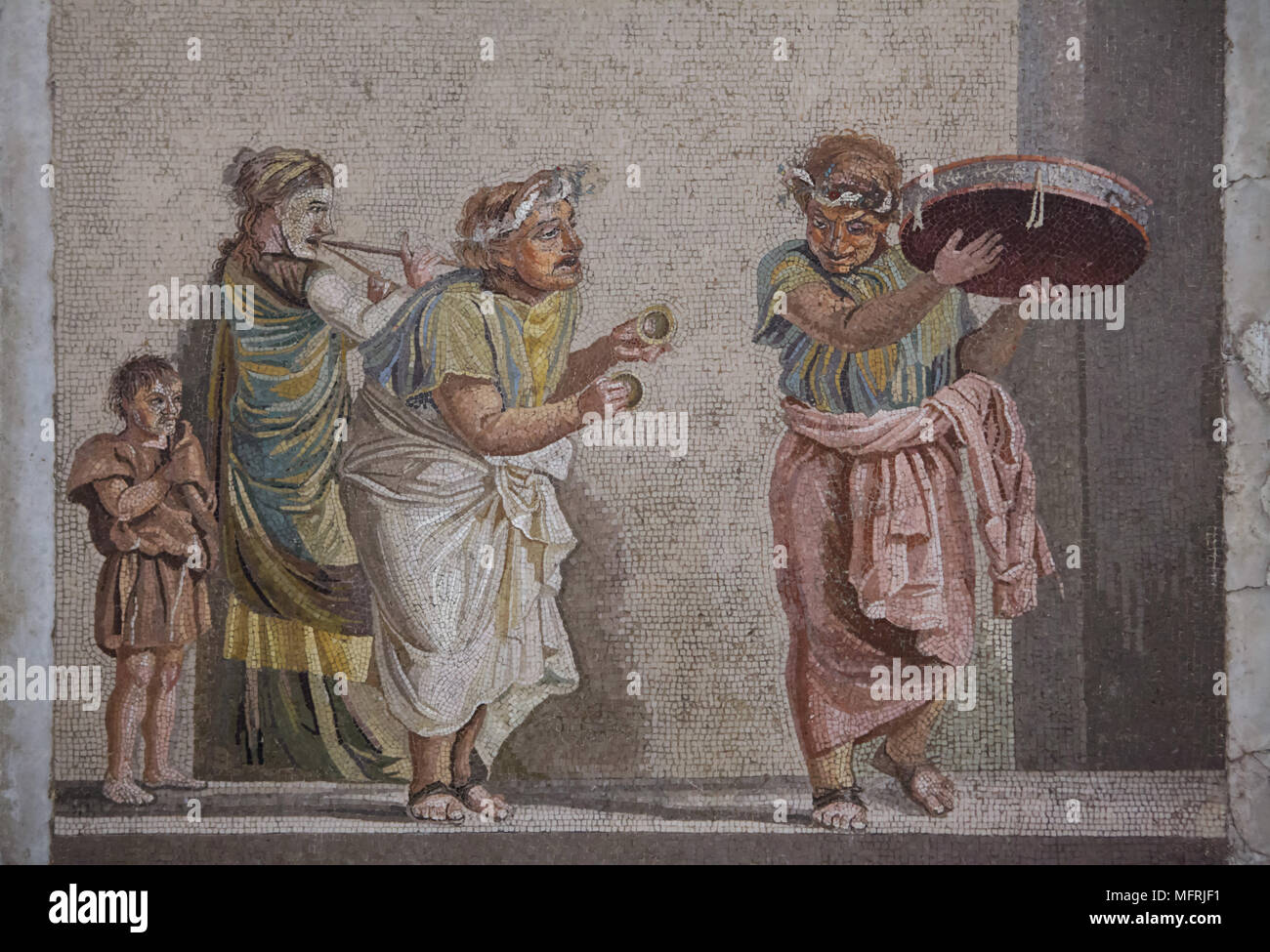 Comedy scene depicted in the Roman mosaic from Villa de Cicero (Villa of Cicero) in Pompeii, now on display in the National Archaeological Museum (Museo Archeologico Nazionale di Napoli) in Naples, Campania, Italy. Street musicians are depicted playing musical instruments often connected with the cult of Cybele: tambourine, small cymbals and double flute (tibia). The mosaic depicts an episode from a comedy, since the figures are wearing theatrical masks. Stock Photo