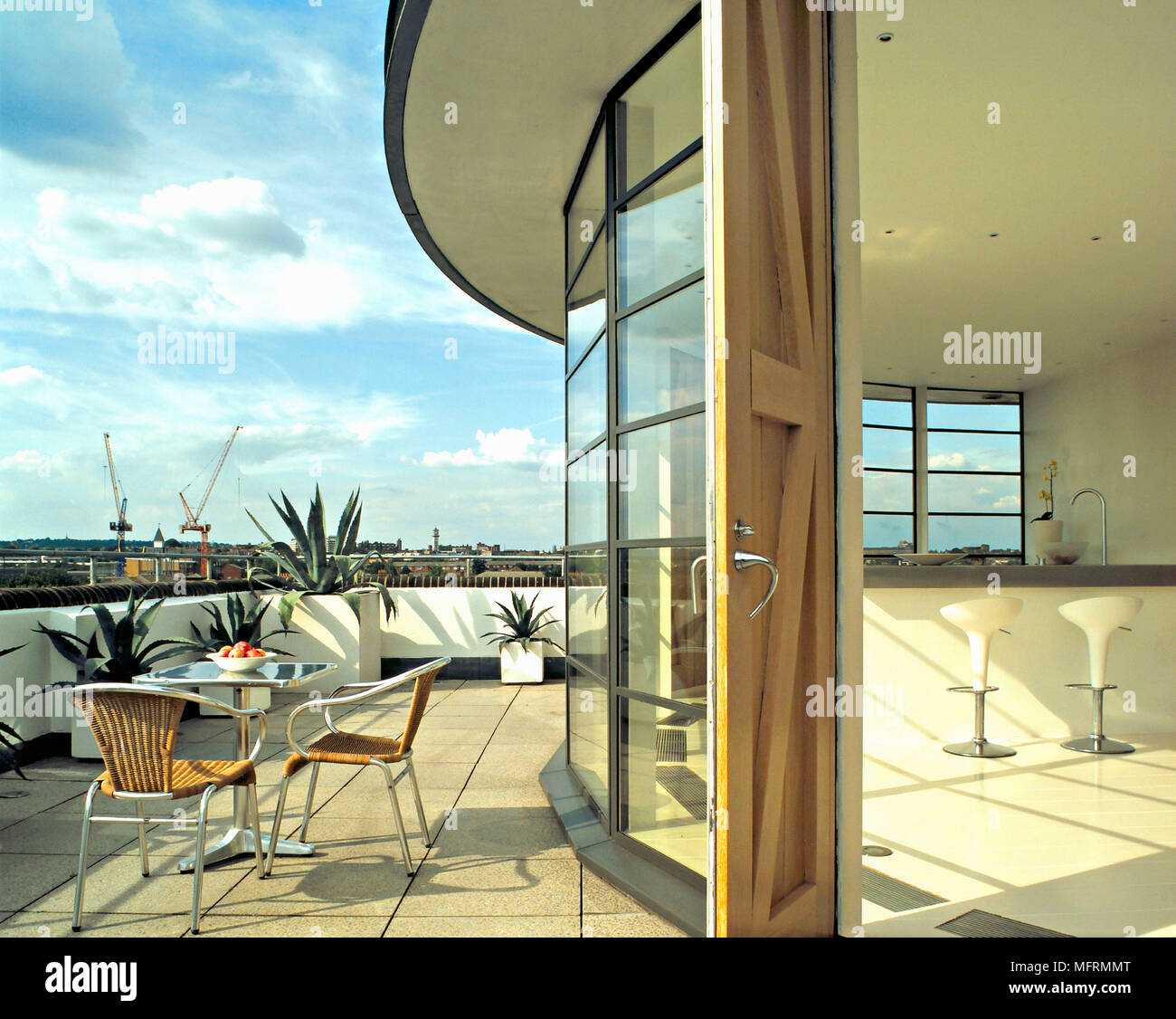 A Modern Roof Terrace Balcony Paved Patio Area Table And Chairs Curving Glass  Wall Leading Off From Kitchen Area