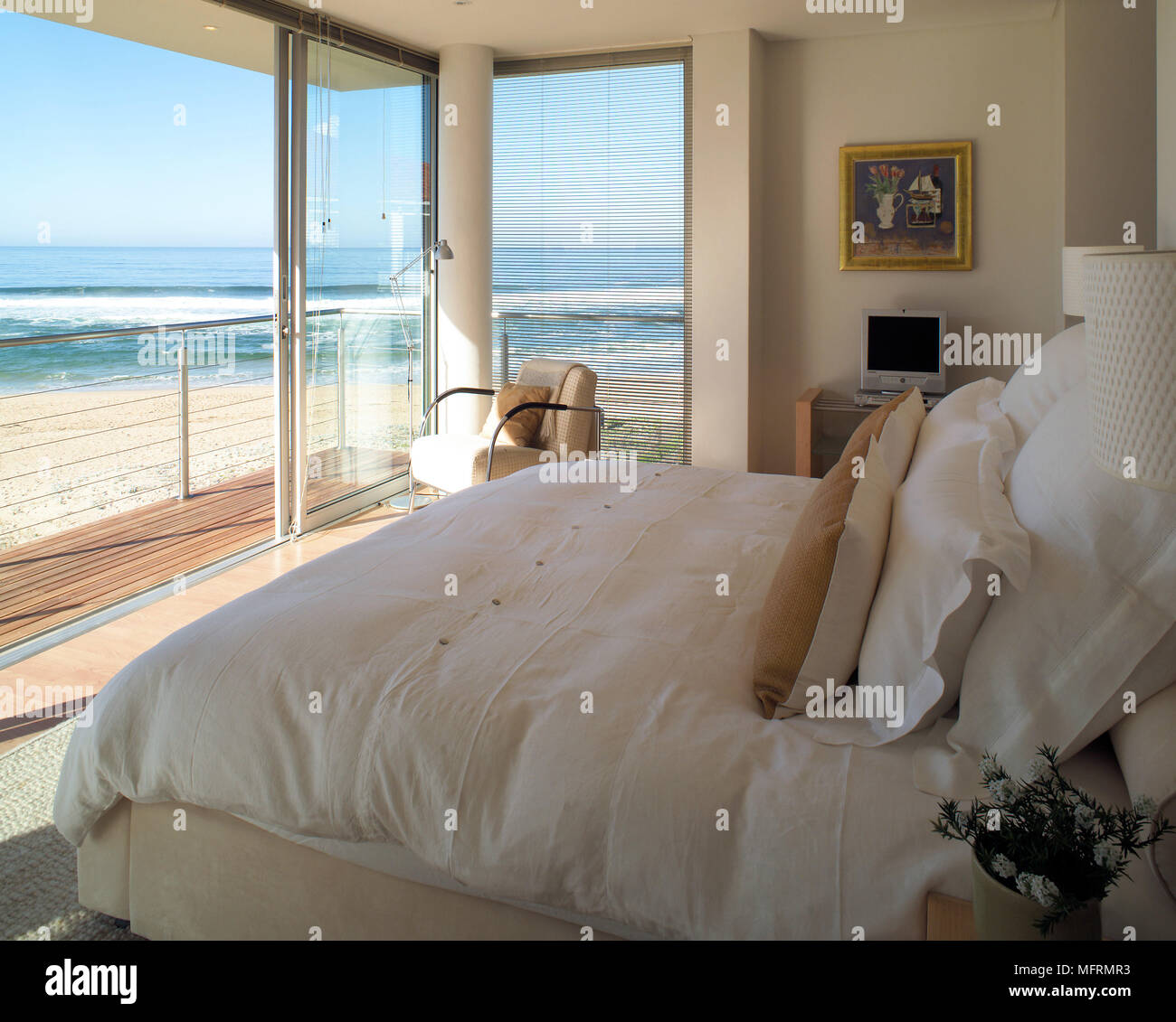 A Modern Neutral Bedroom With Double Bed Sliding Glass Doors Opening