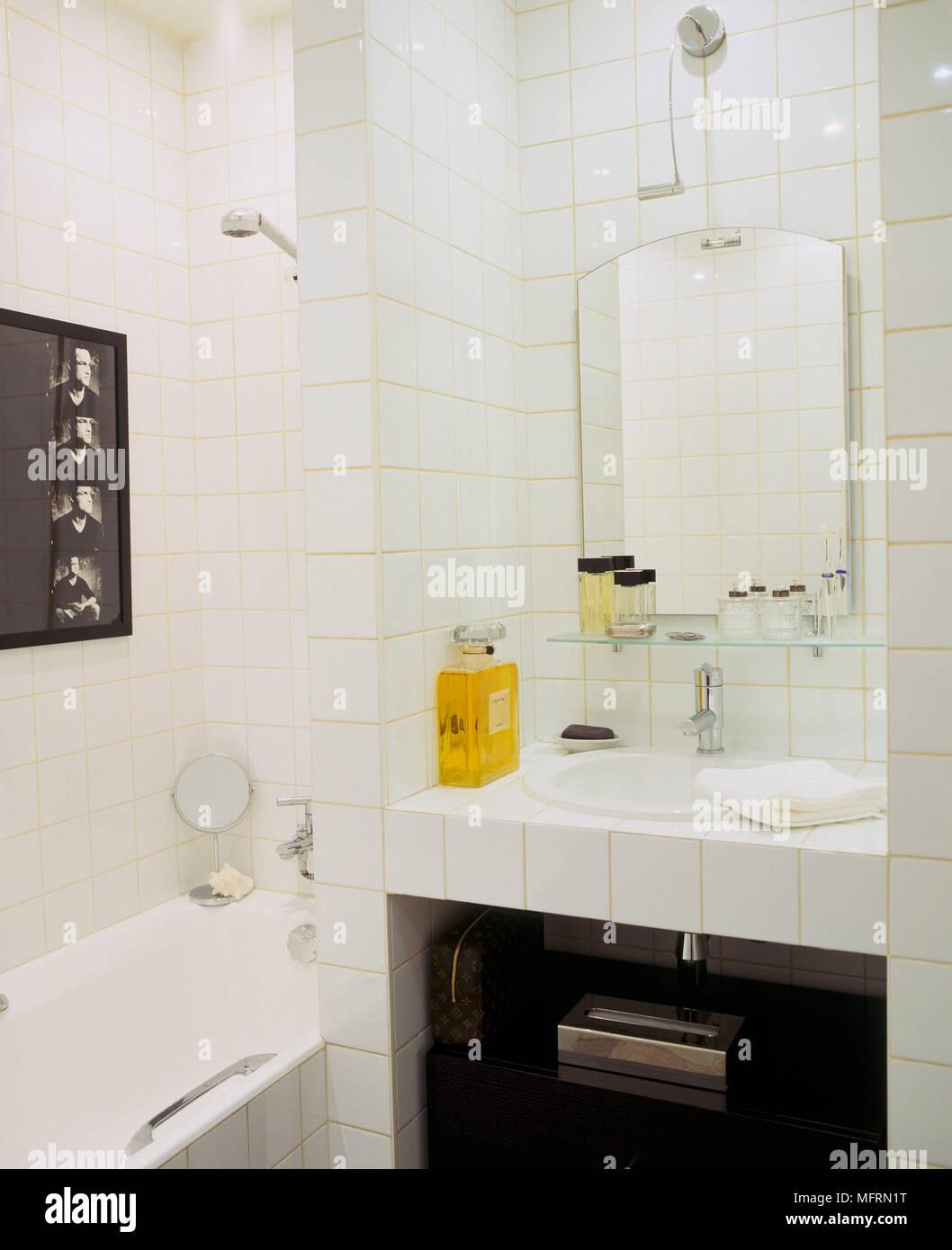 A detail of a modern white bathroom with tiled walls washbasin set ...