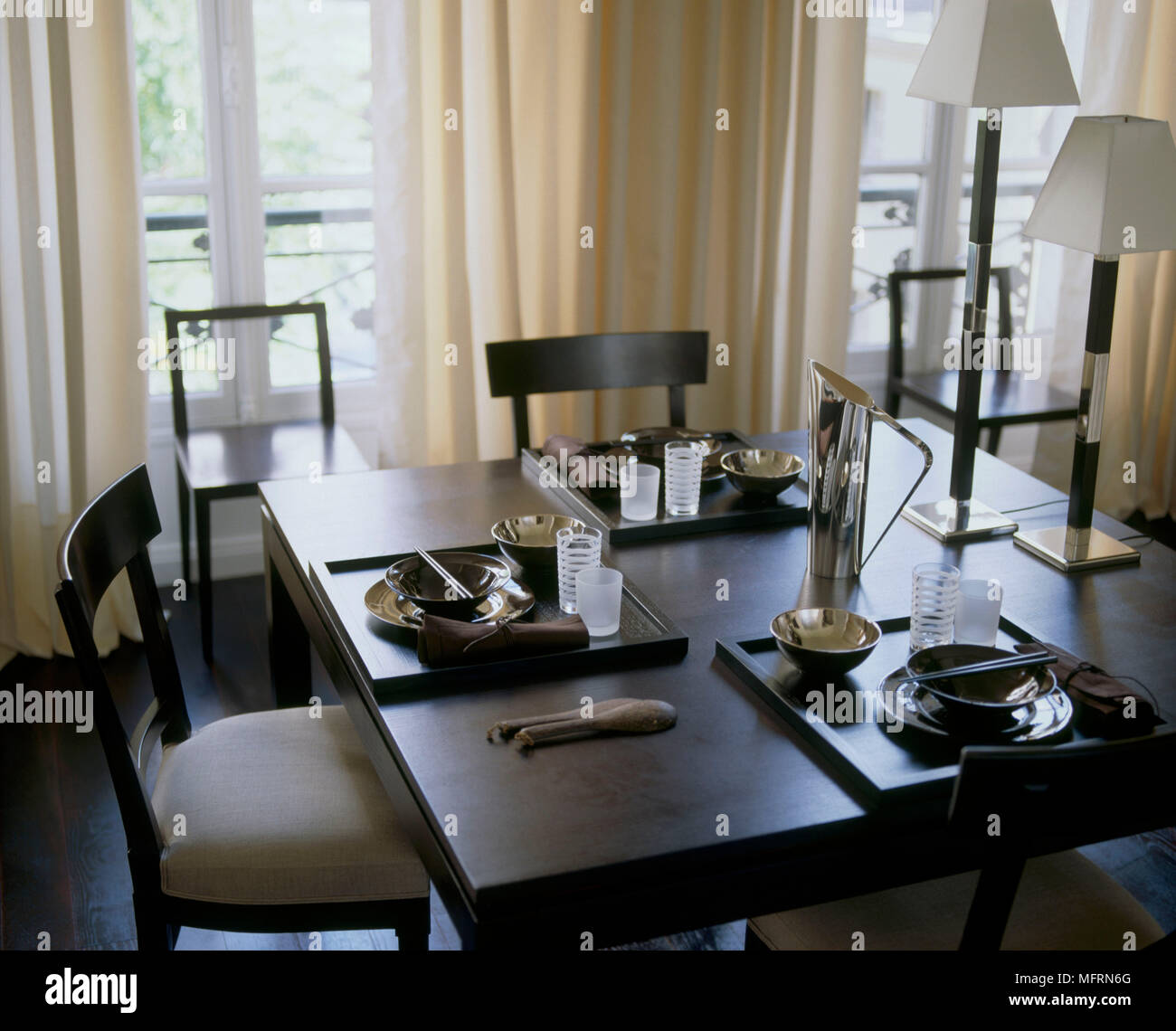 A Detail Of A Modern Dining Room Square Wood Table Upholstered Chairs Table  Setting Open Curtains