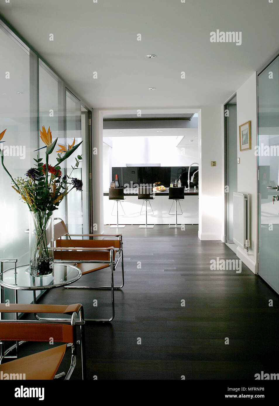 Pair of Marcel Breuer Wassily chairs either side of Elieen Gray table in modern hallway - Stock Image