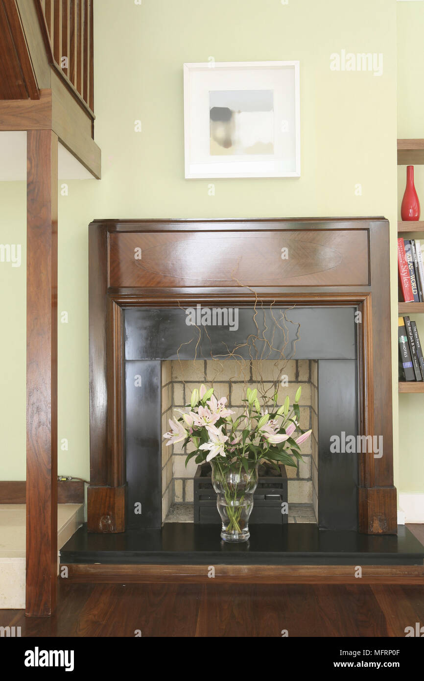 762c48f3e7a3 Flower arrangement in glass vase in fireplace hearth - Stock Image