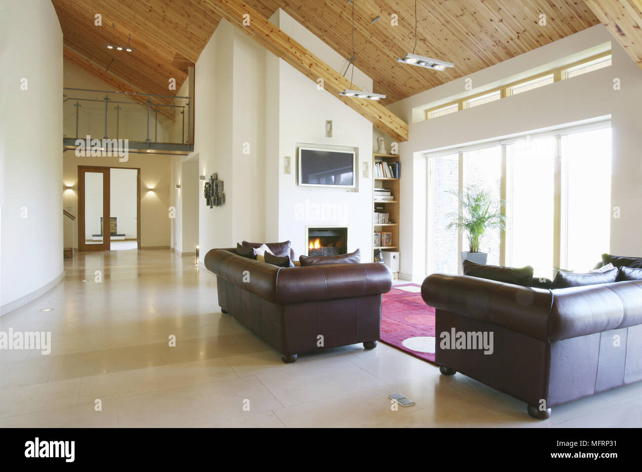 Pair Of Leather Sofas In Front Of Fireplace With Lit Fire In