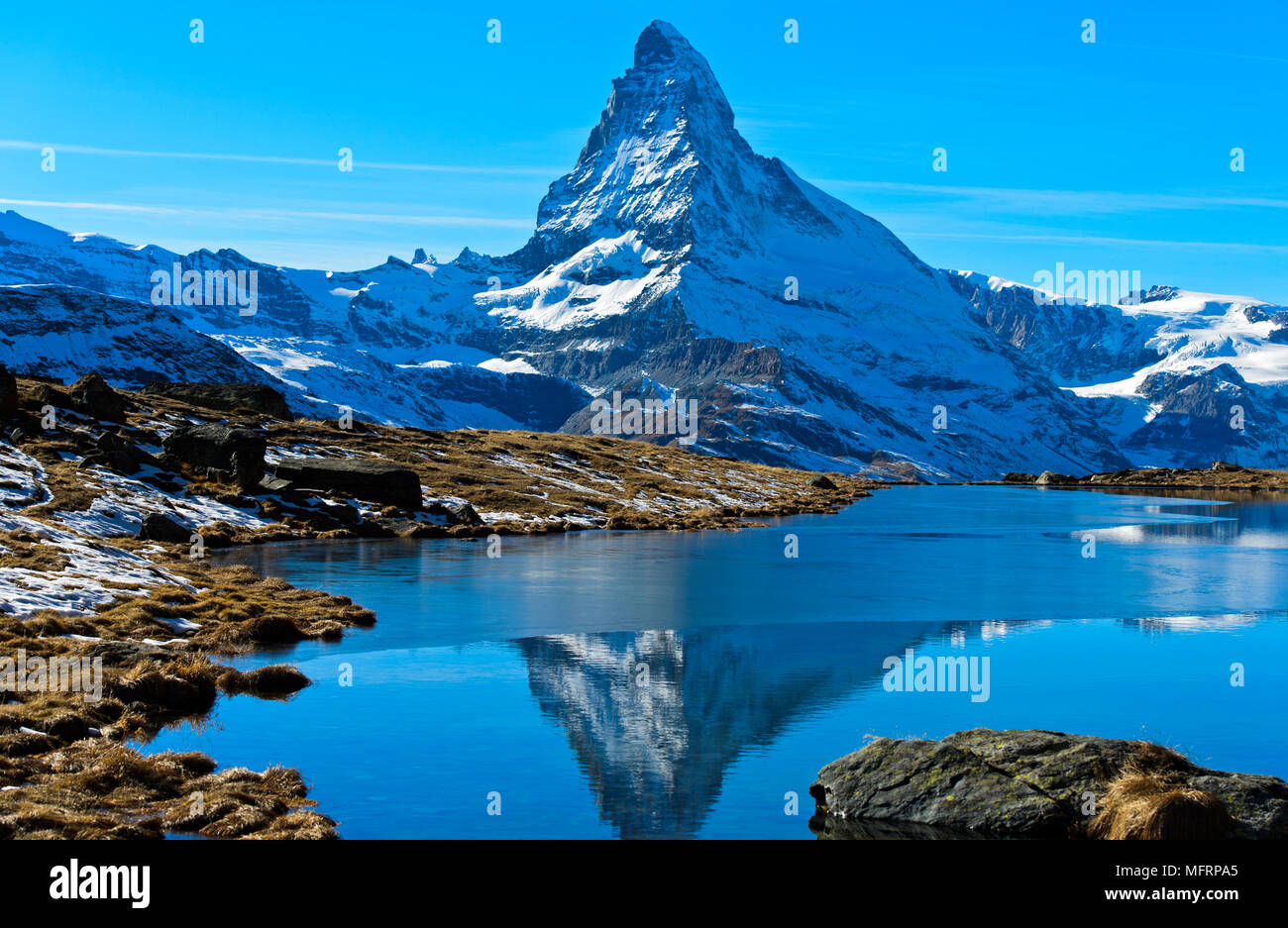Snowy Matterhorn reflected in the partly frozen Stellisee, Zermatt, Valais, Switzerland - Stock Image