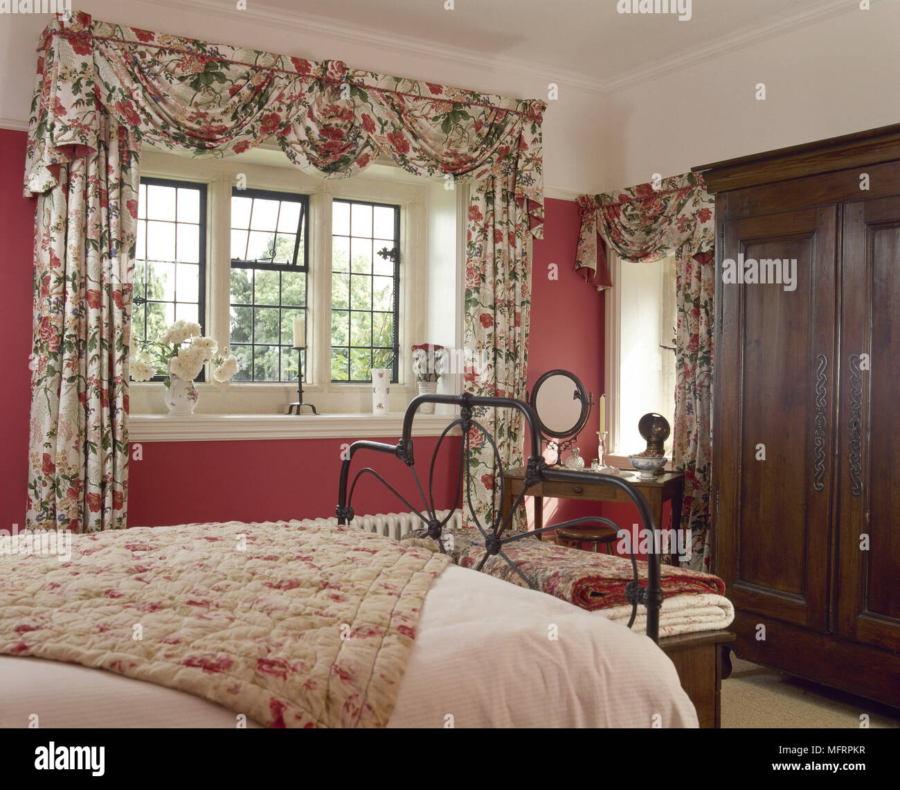 Country Bedroom With Floral Swag Curtains Wrought Iron Bed And A Dark Wood Wardrobe Stock Photo Alamy