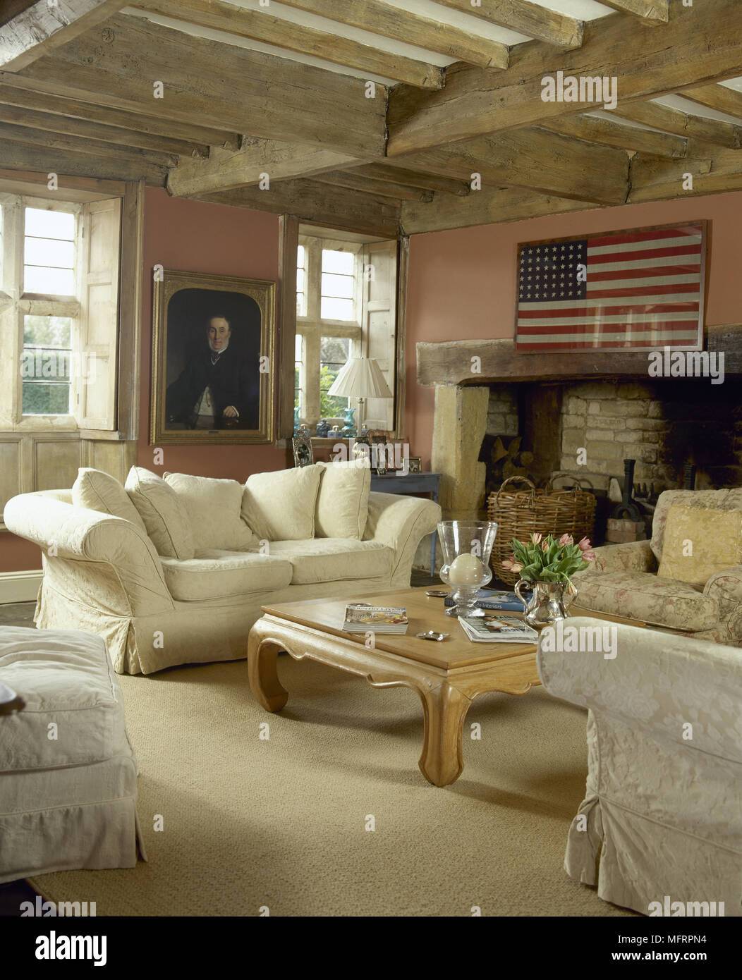 Rustic, Country Sitting Room With Wood Beamed Ceiling, Framed American Flag,  And A Comfortable Seating Area In Front Of An Inglenook Fireplace.