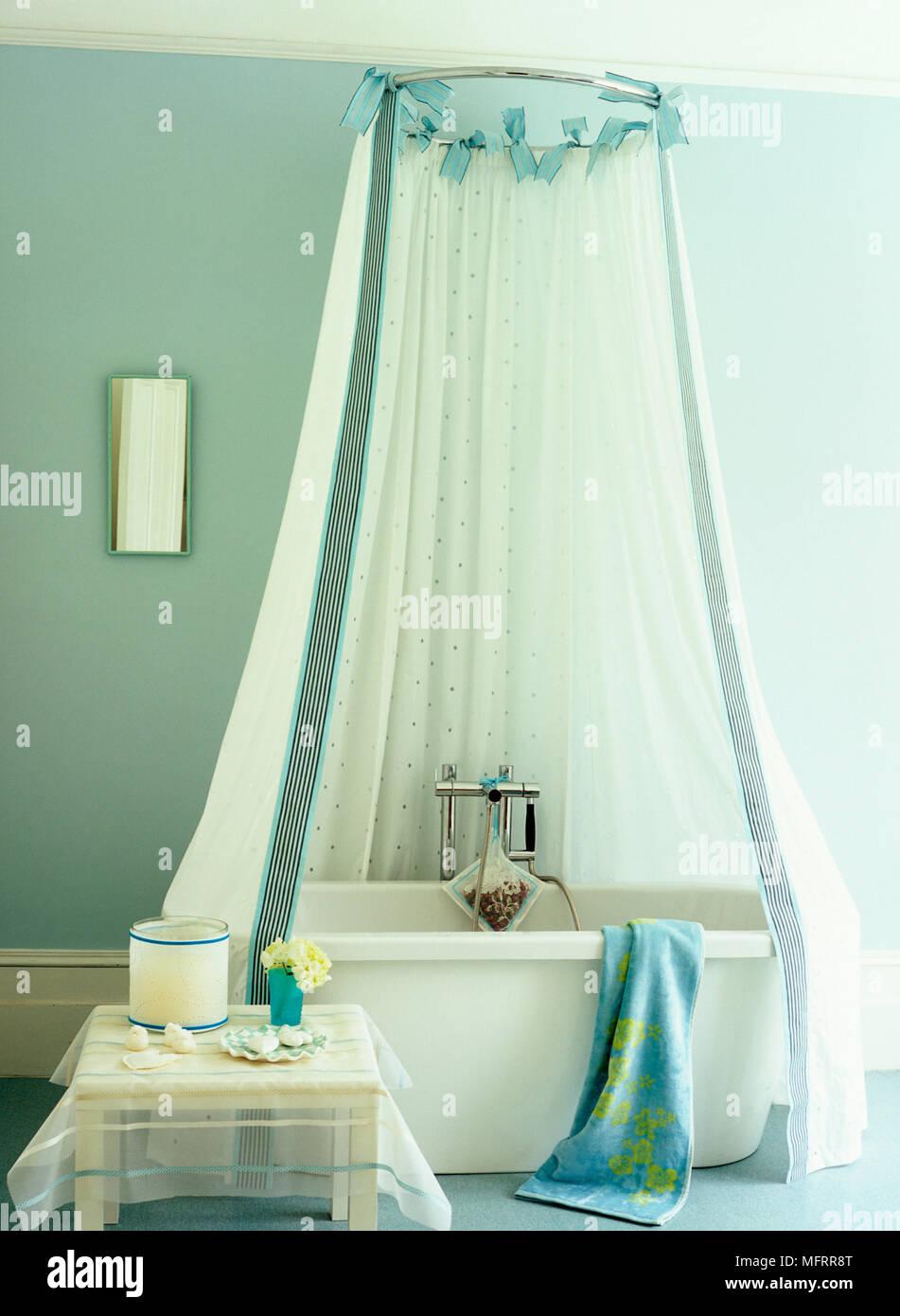 Shower Curtain Above Freestanding Bathtub In Blue Bathroom Stock