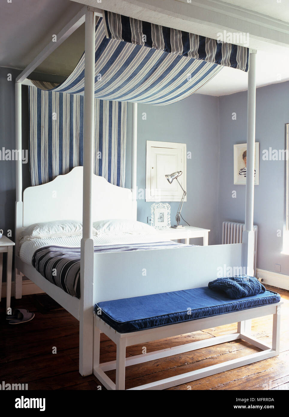 White Wood Four Poster Bed With Blue Stripe Fabric Canopy In Modern Bedroom Stock Photo Alamy