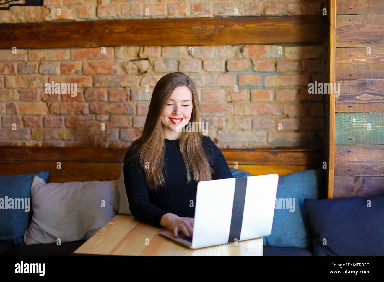 Smiling female person with red lips using laptop at cafe. - Stock Image