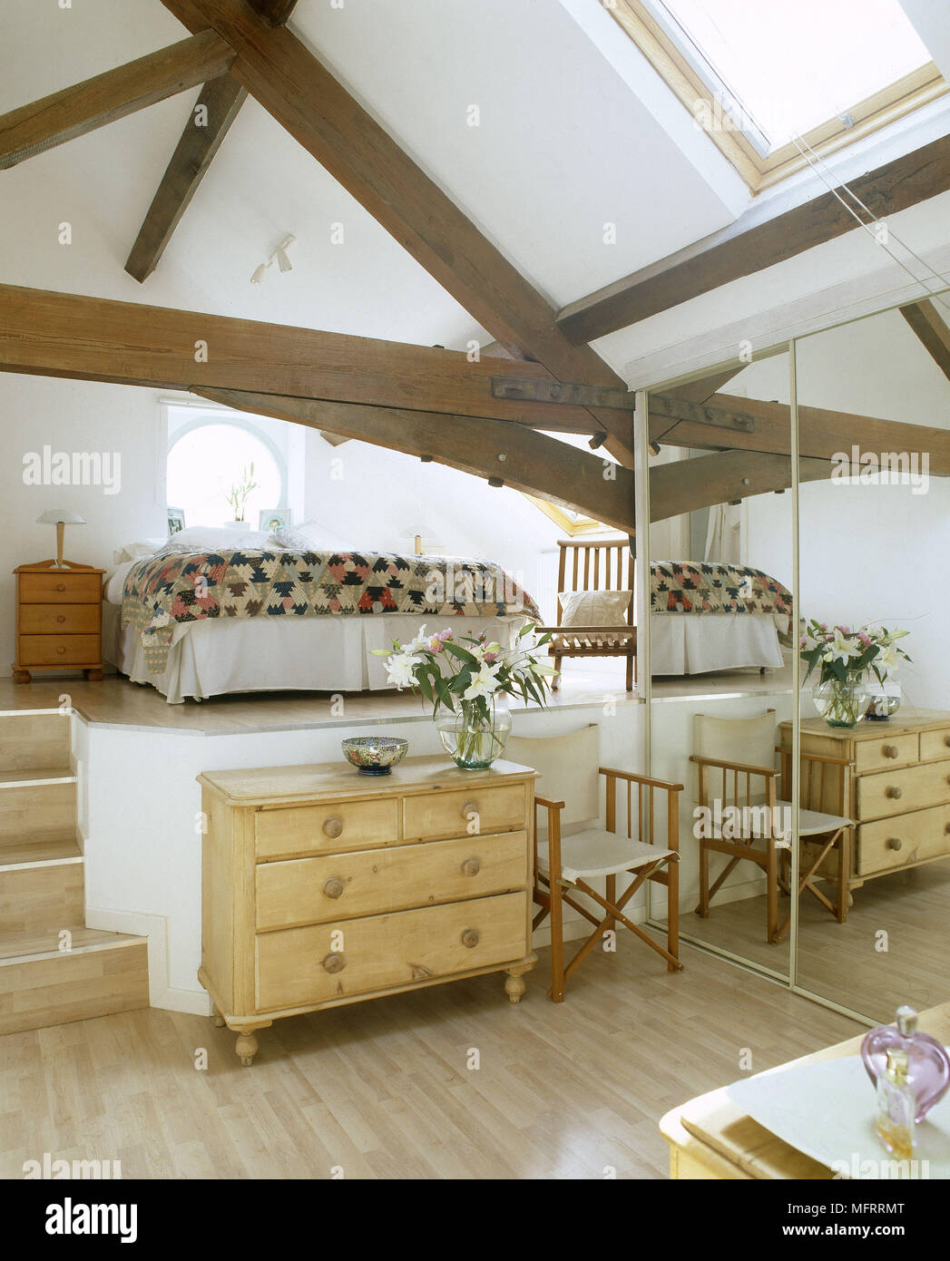 A Modern Country Style Split Level Bedroom With Exposed Beams Bed Pine  Chest Of Drawers Mirrored Wardrobes