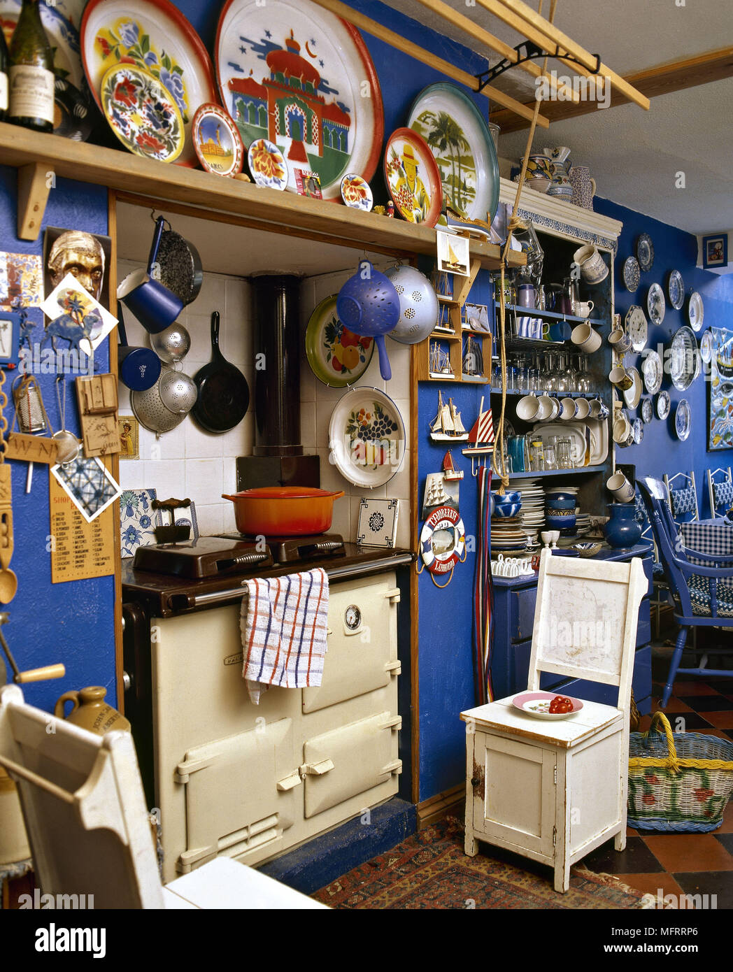 A traditional country style blue kitchen with cream Aga ceramic wall plates Stock Photo