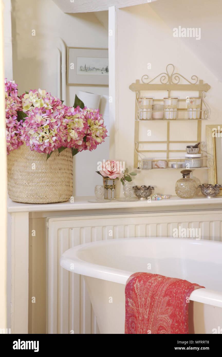 Basket of pink hydrangeas on shelf above radiator next to ...