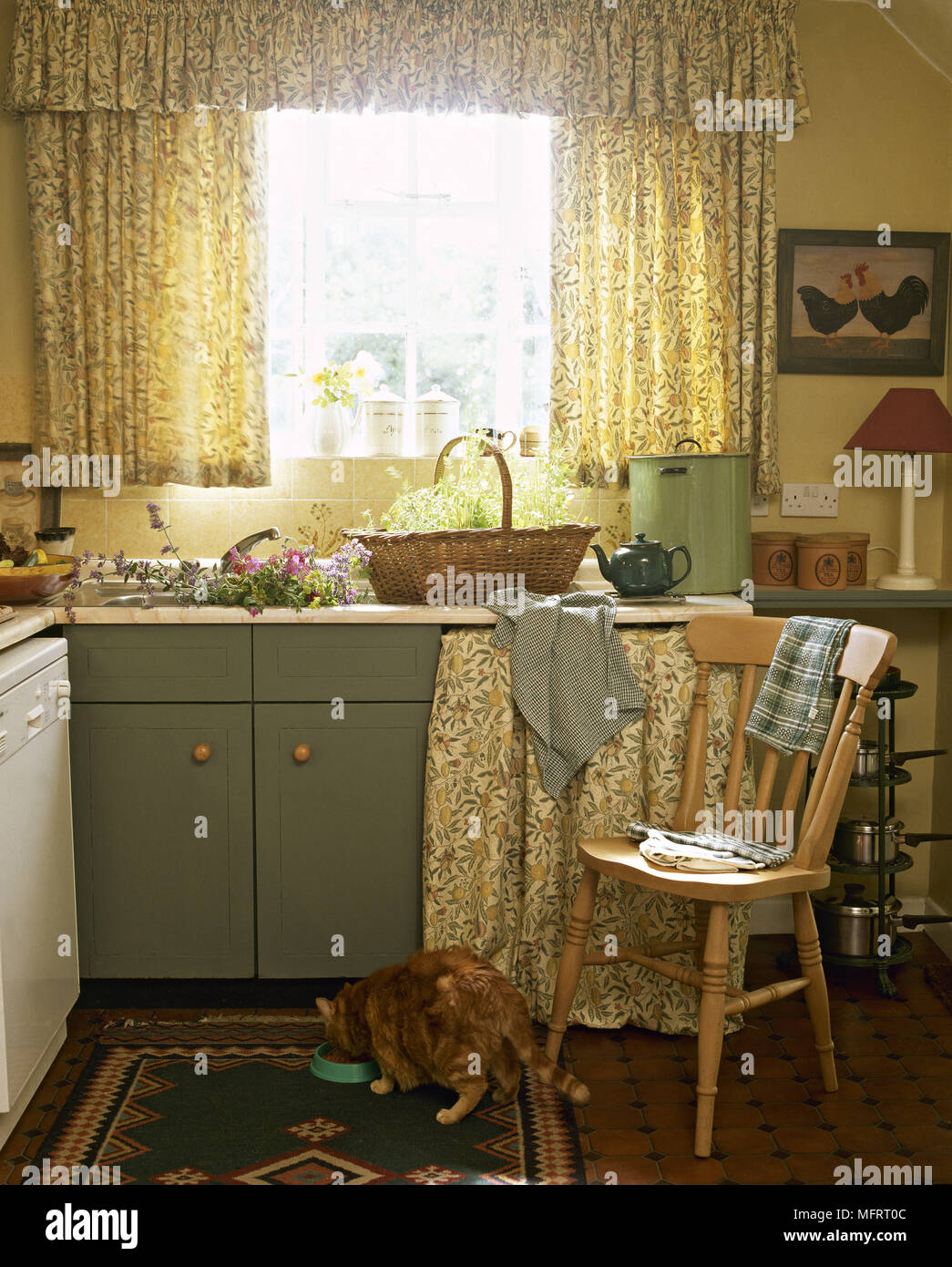 Country Yellow Kitchen With Green Cabinets Floral Curtains And A Cat Eating From A Bowl On The Floor Stock Photo Alamy