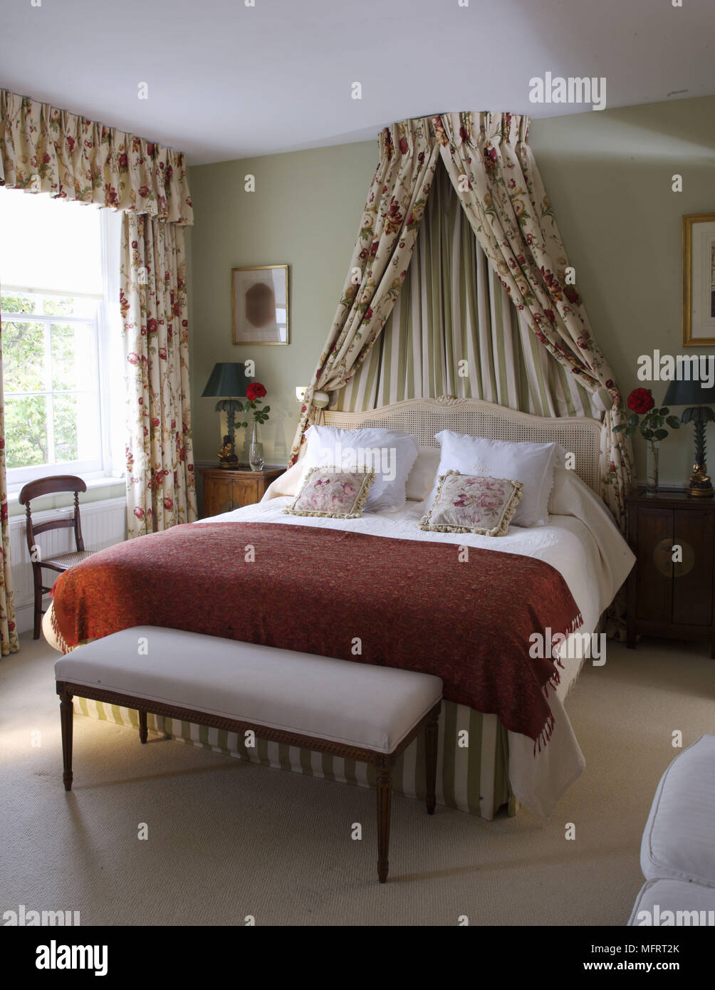 Double bed with floral canopy and coordinating furnishings - Stock Image