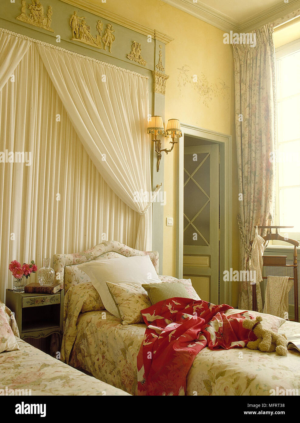 Draped curtains on wall over twin beds in yellow bedroom ...