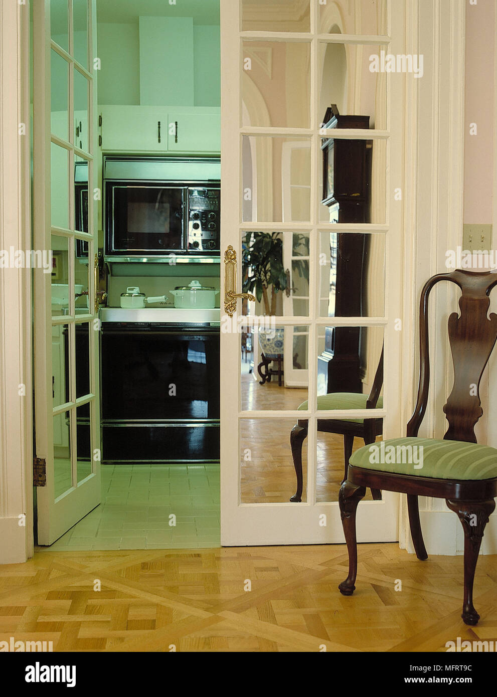 Open Mirrored French Doors With Kitchen Beyond Stock Photo