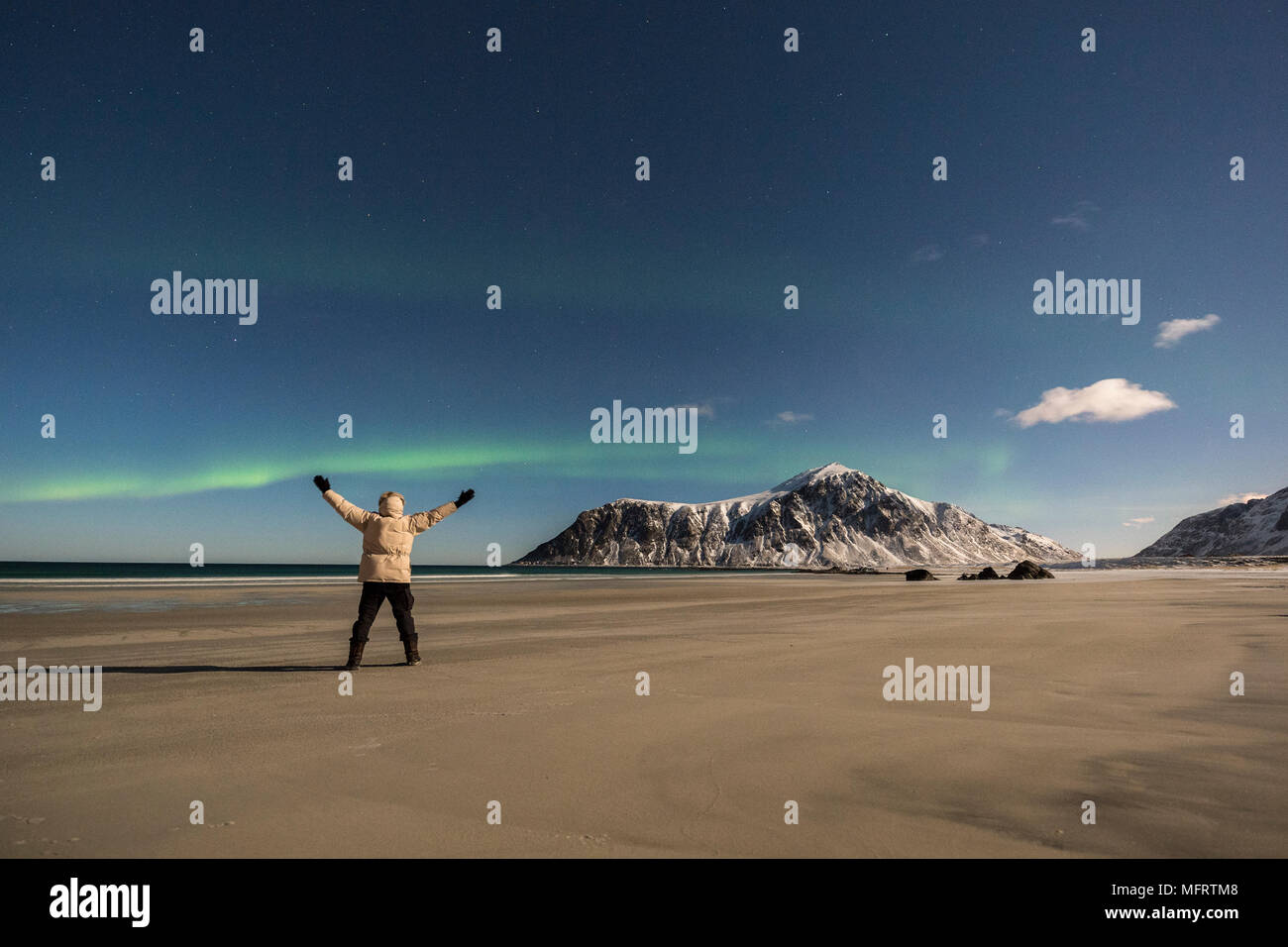 Man watches northern lights on the beach of Skagsanden, Aurora Borealis, Skagsanden, Lofoten, Norway - Stock Image