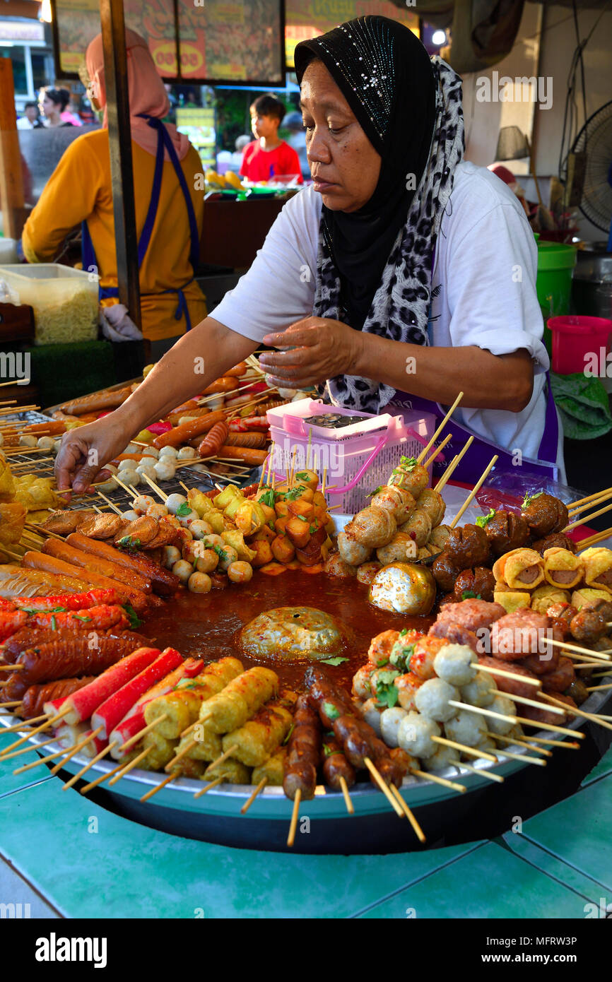 Saleswoman at the market stand with different skewers with meat and seafood, seafood, typical for the country - Stock Image