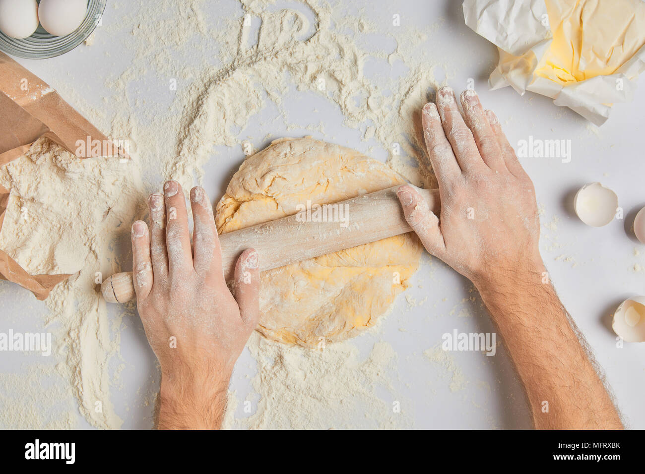cropped image of chef rolling dough with rolling pin - Stock Image