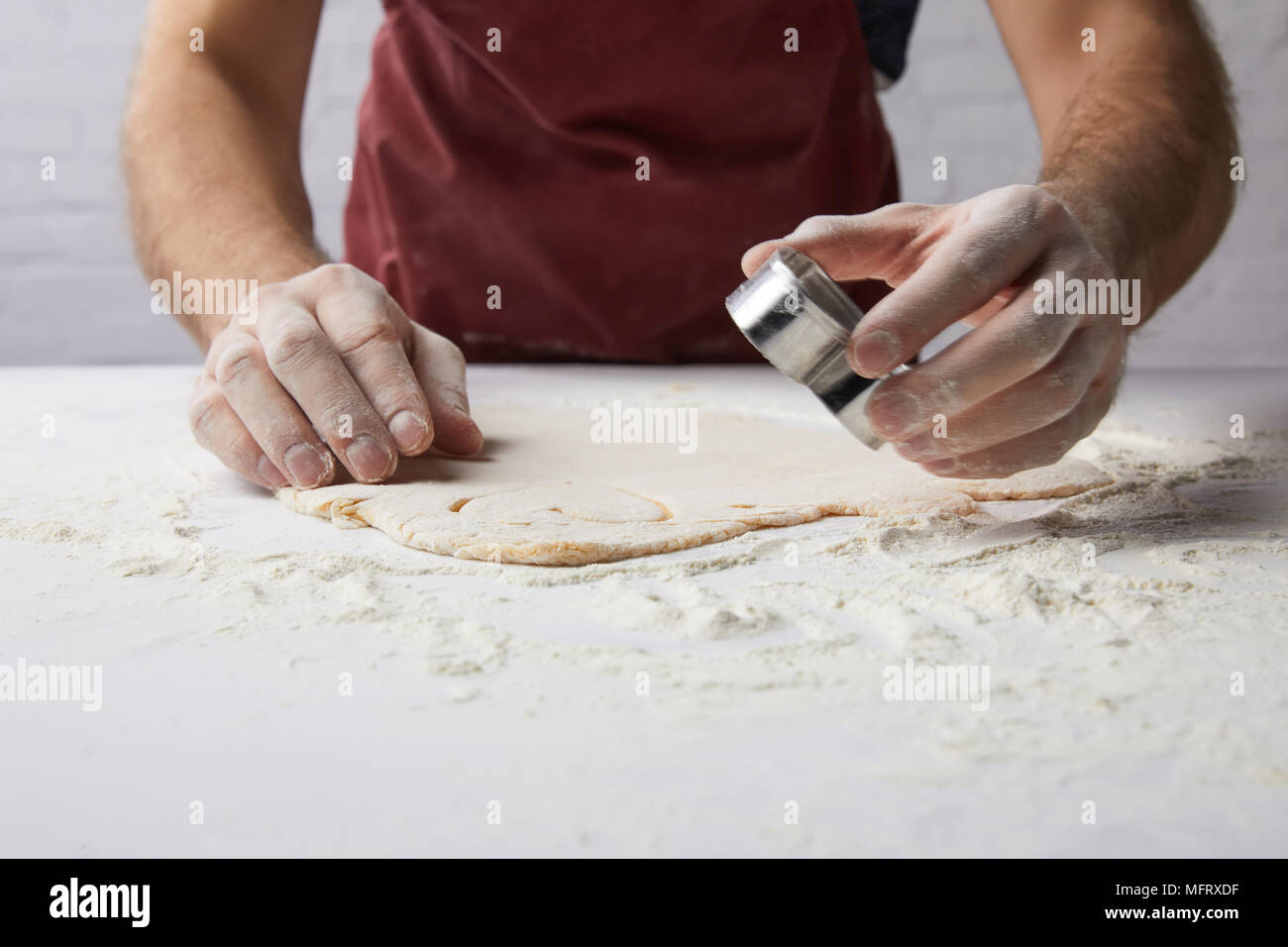 cropped image of chef preparing heart shaped cookies with dough mold, valentines day concept - Stock Image