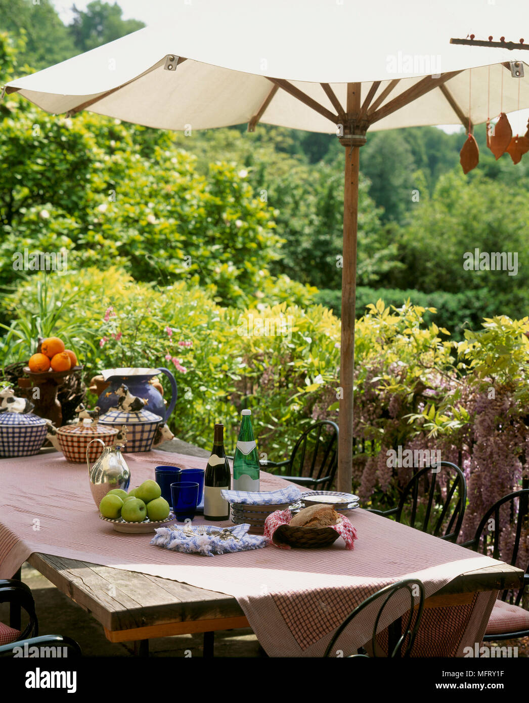 Outdoor wooden table in a garden setting, chairs and parasol, table ...