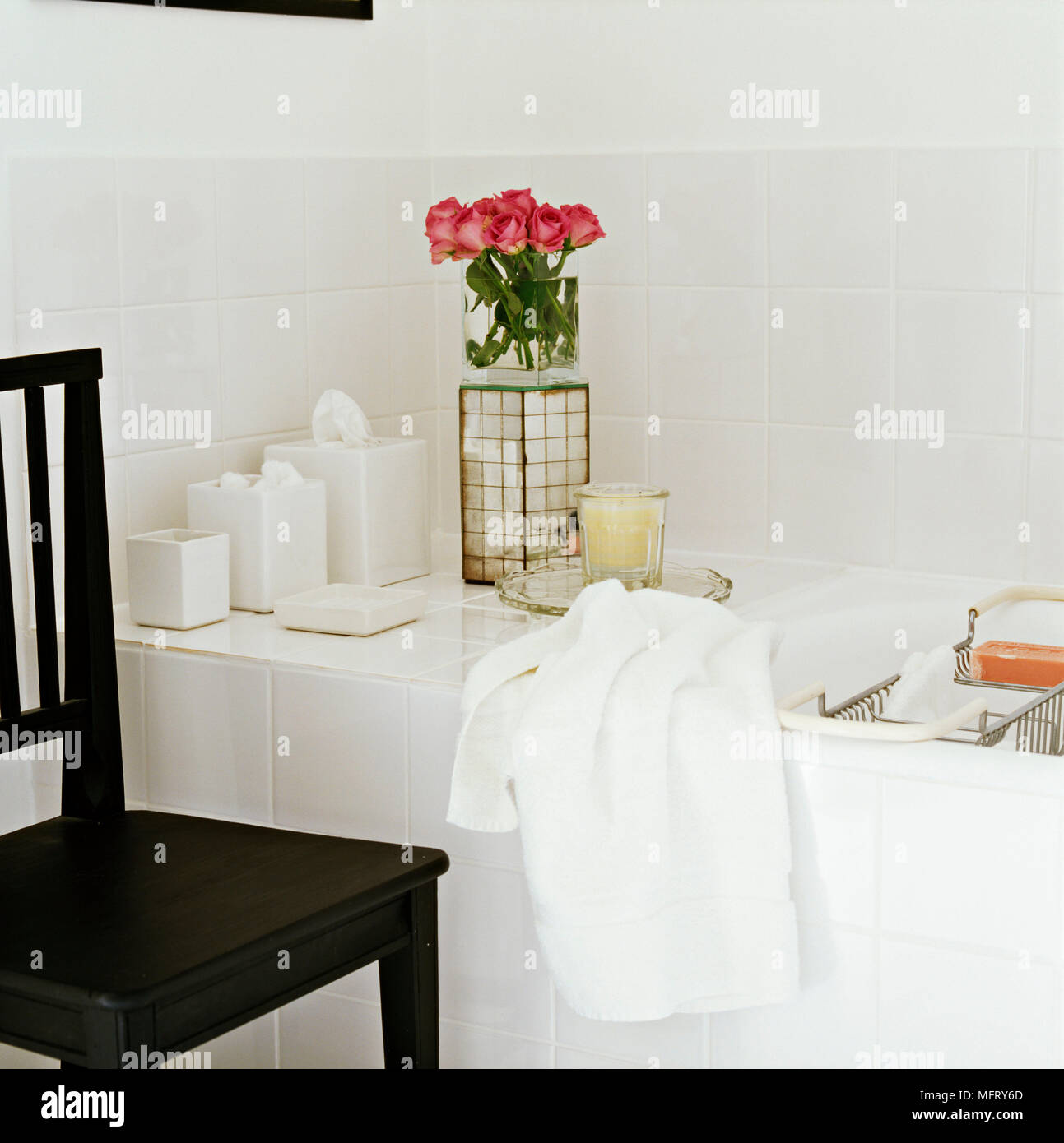 A detail of a modern white bathroom showing a bath with ceramic tile ...