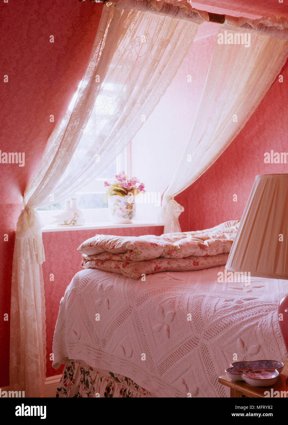 A Detail Of Traditional Country Cottage Red Bedroom With Dormer Window Dressed Lace Curtains Bed Quilt