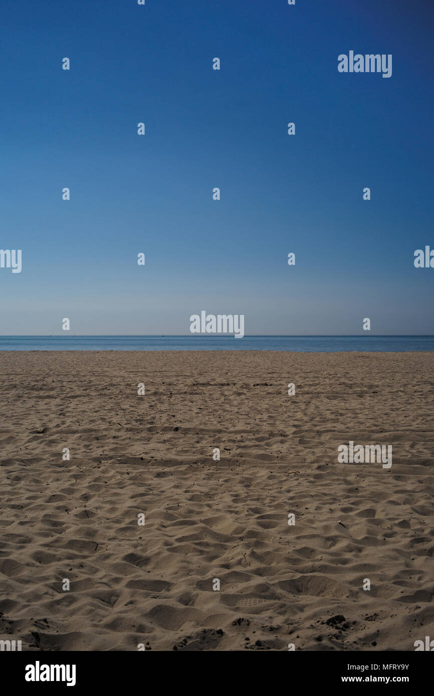 A landscape of a empty sandy beach, showing a horizon with a blue sky and sea with a sandy foreground on a sunny hot day. Stock Photo