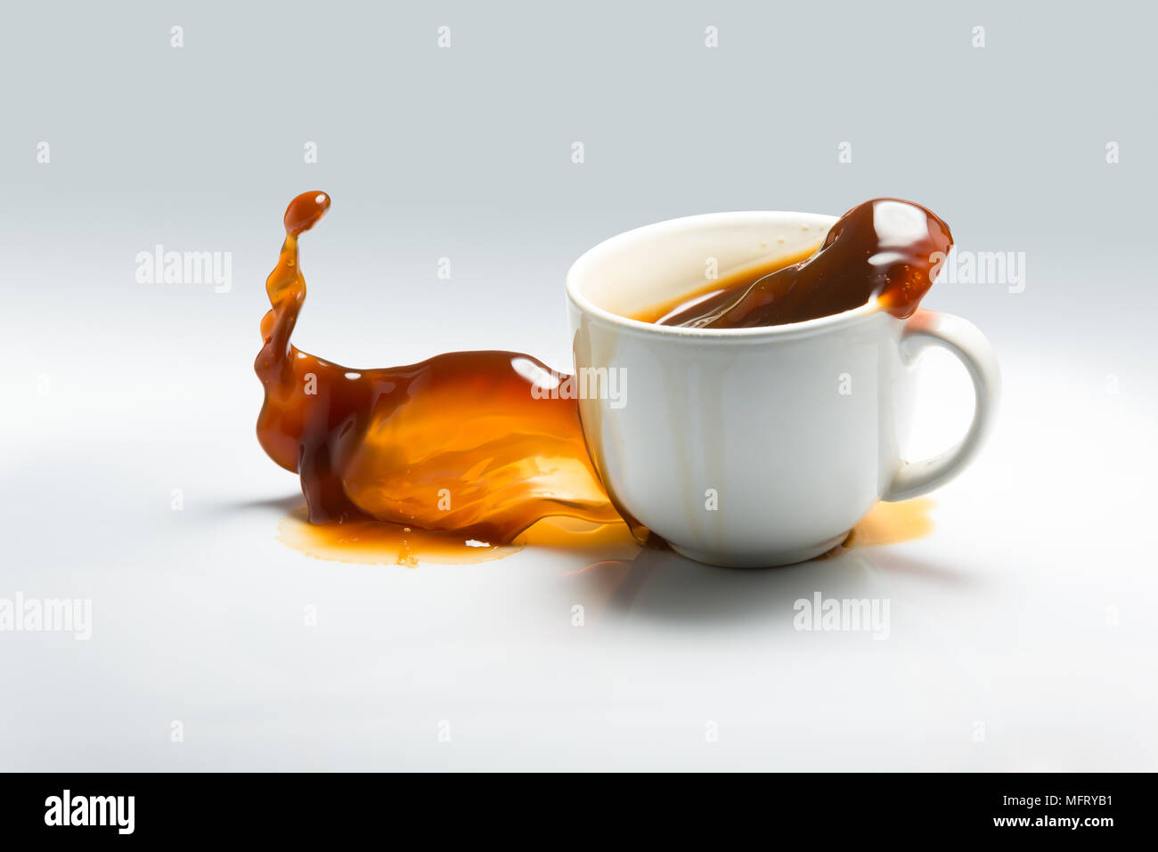 Falling and spilling of a cup of coffee against a white background - Stock Image