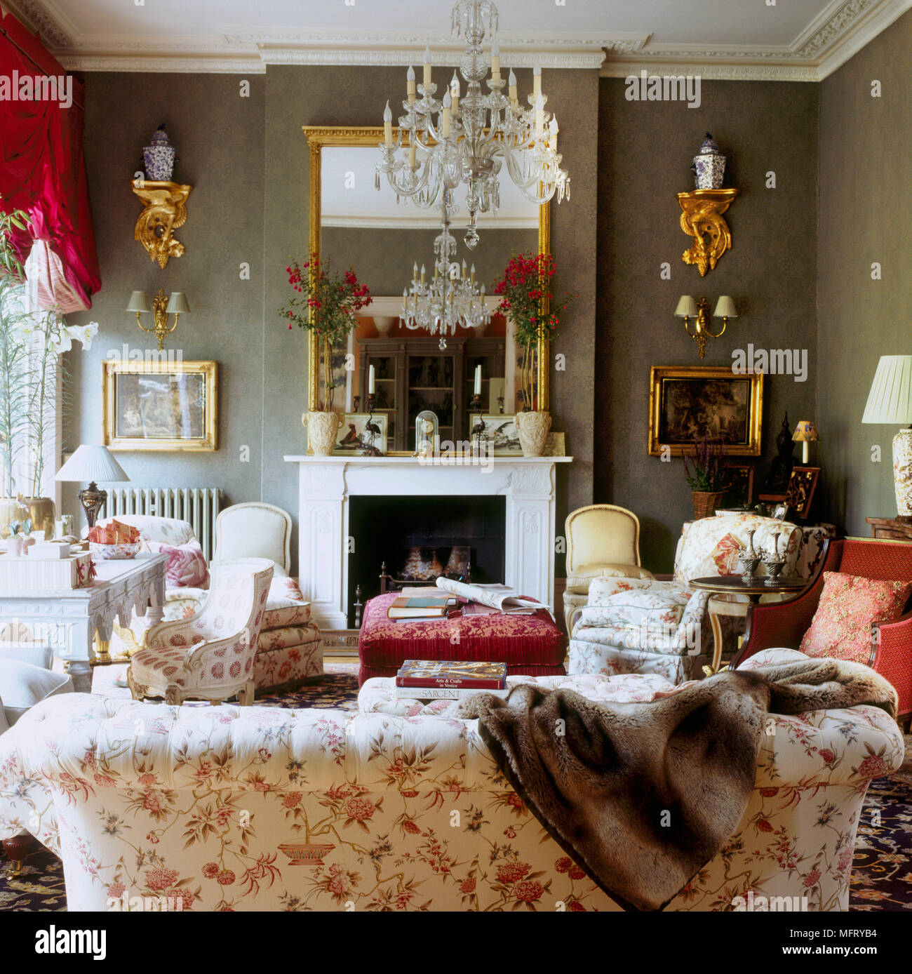 A Grand Traditional Sitting Room With Fireplace Red Floral Upholstered Sofa  Armchairs Gilt Mirror Chandelier