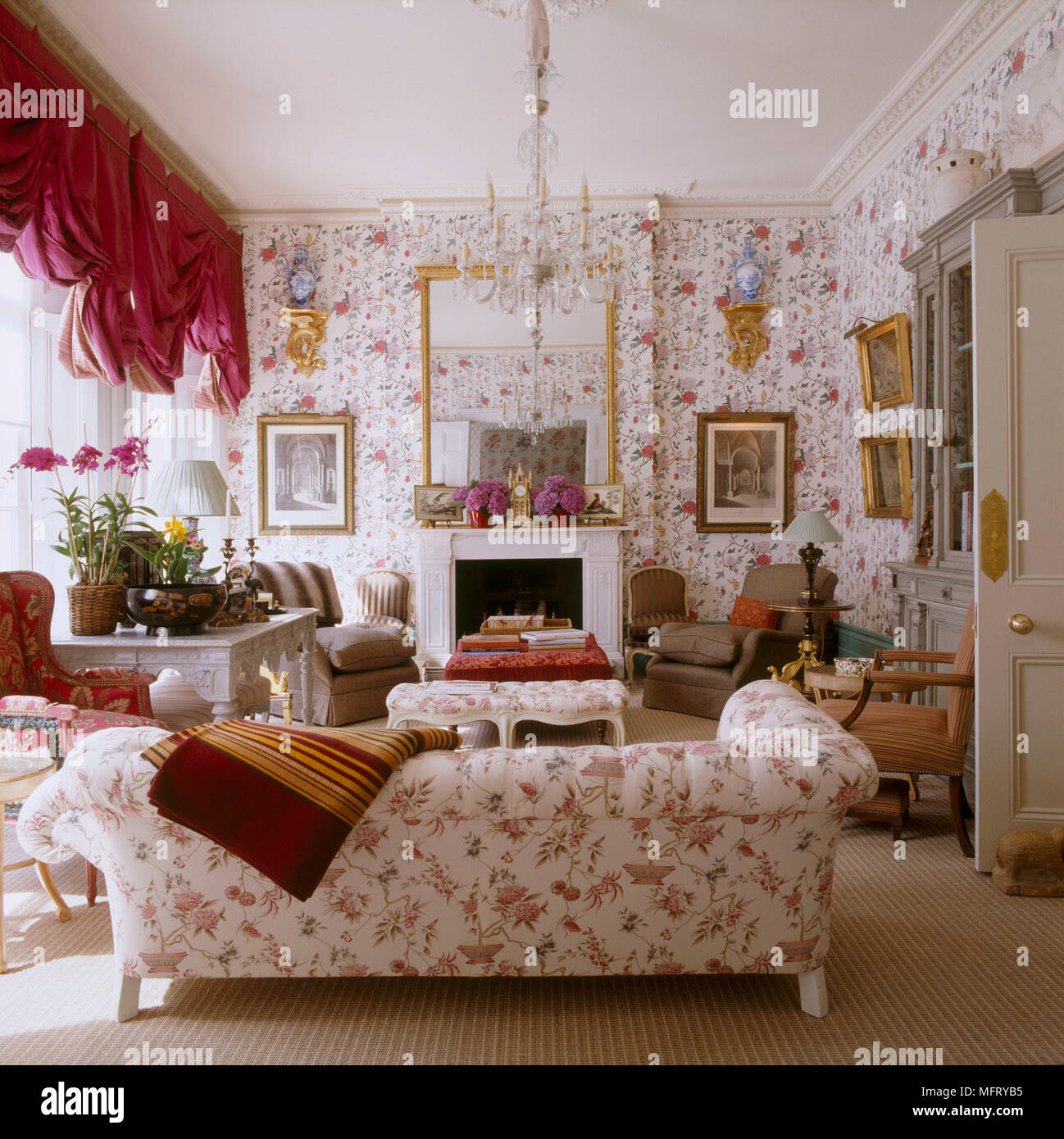 A Grand Traditional Sitting Room With Fireplace Red Floral Wallpaper  Upholstered Sofa Swag Curtains