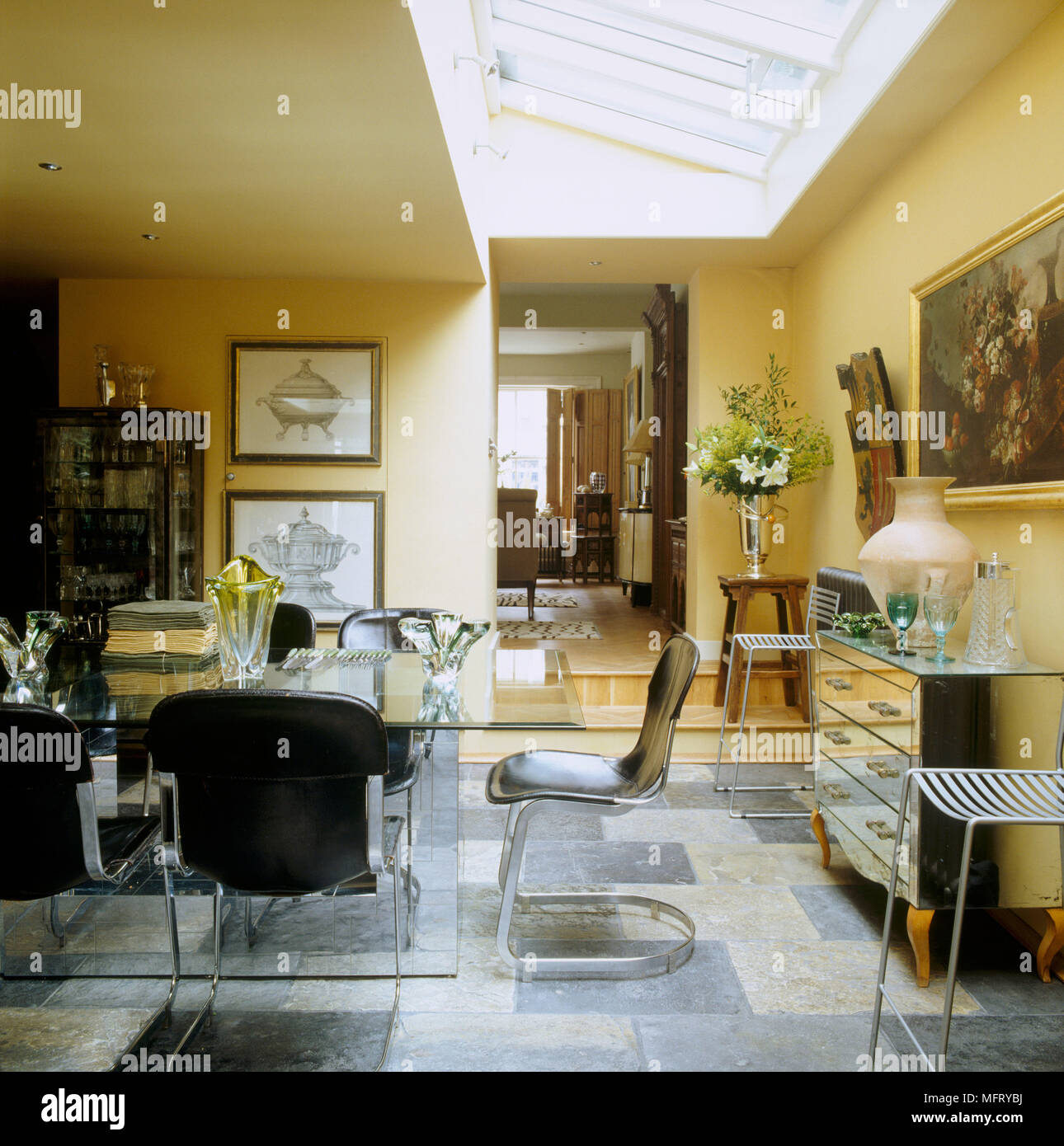A Modern Open Plan Yellow Dining Room Glass Table Chairs Mirrored Chest Of Drawers Stools Tiled Floor Stock Photo Alamy