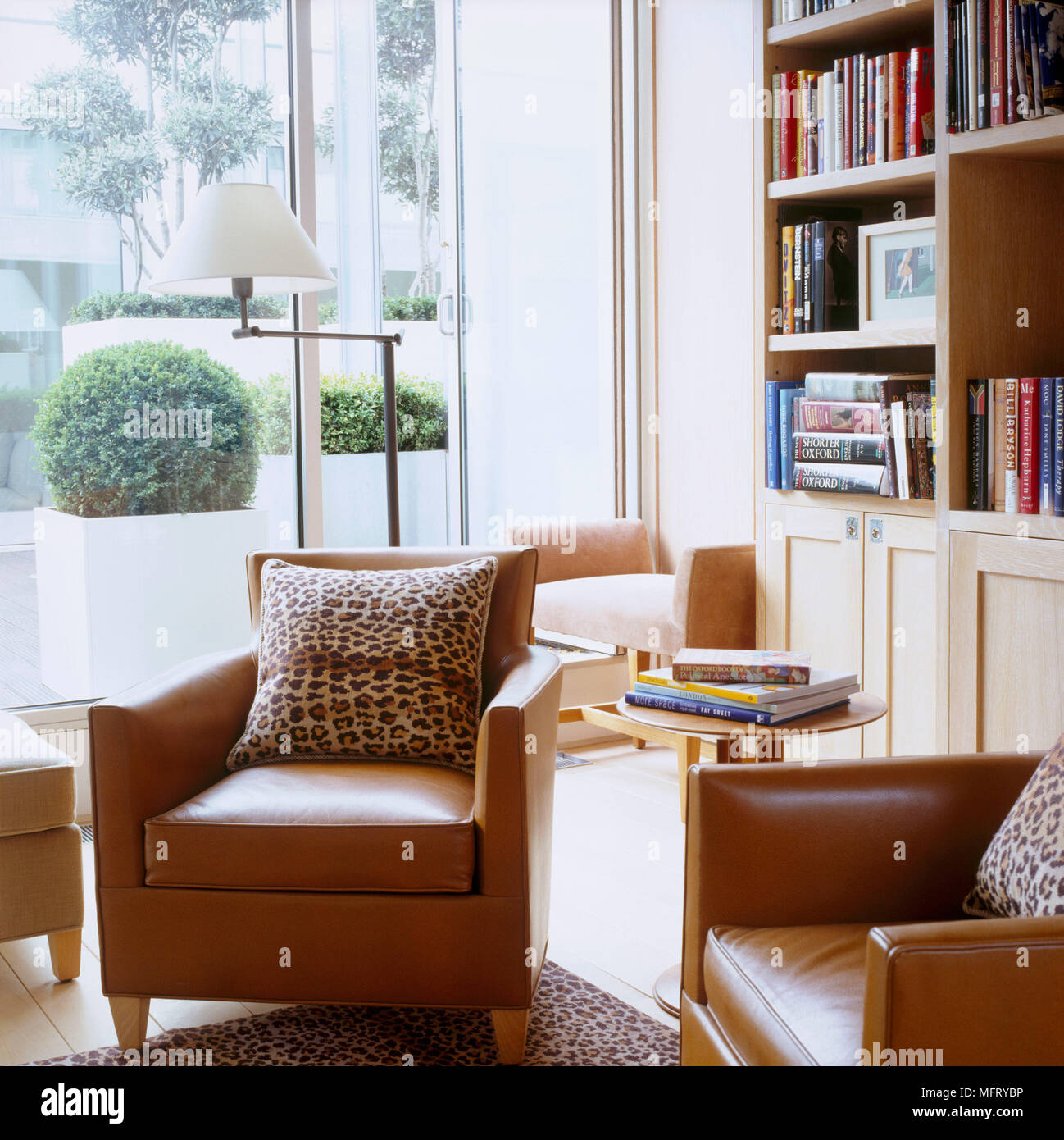 Picture of: A Modern Sitting Room With Tan Leather Armchairs Bookcase Round Side Table Floor Lamp Leopard Skin Print Cushions Stock Photo Alamy